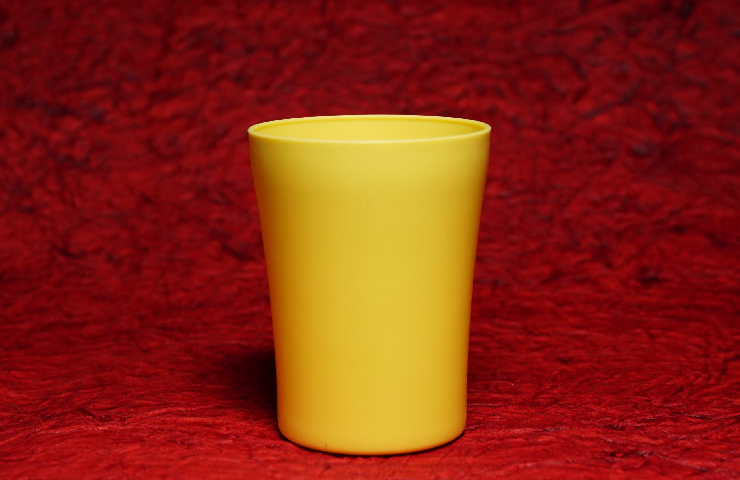 A yellow tumbler in red background