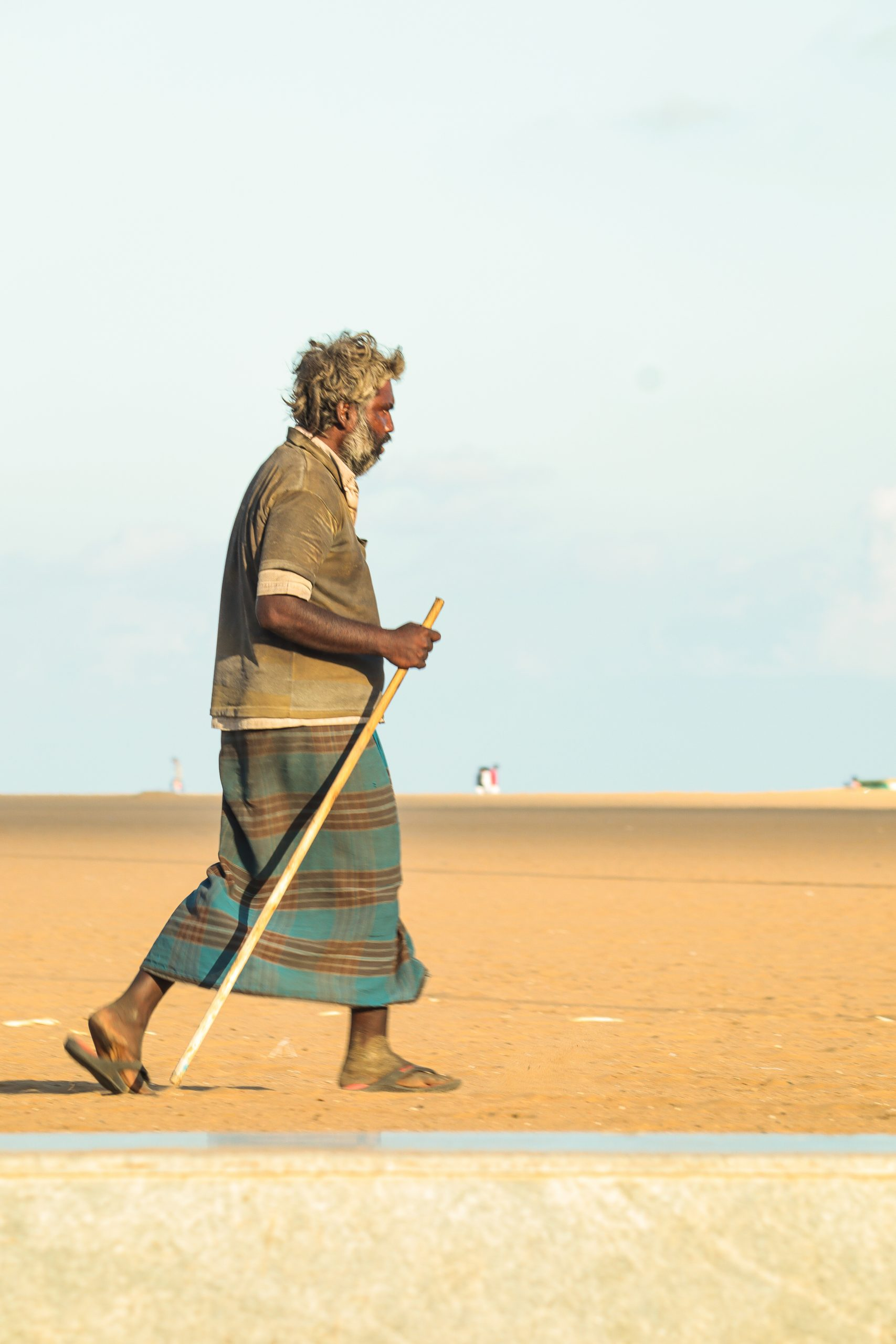 An old man walking in sand