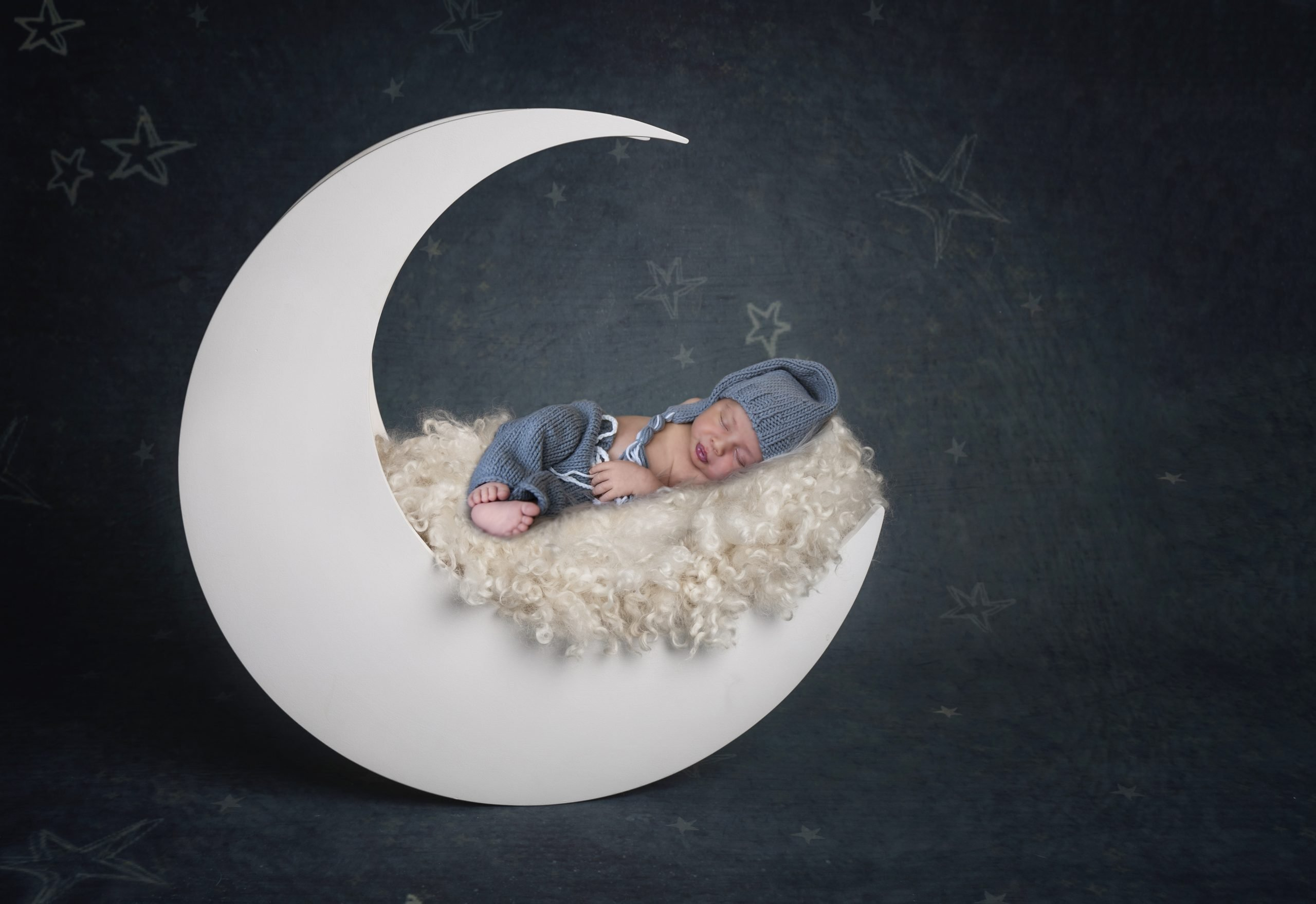 Cute baby sleeping on a moon