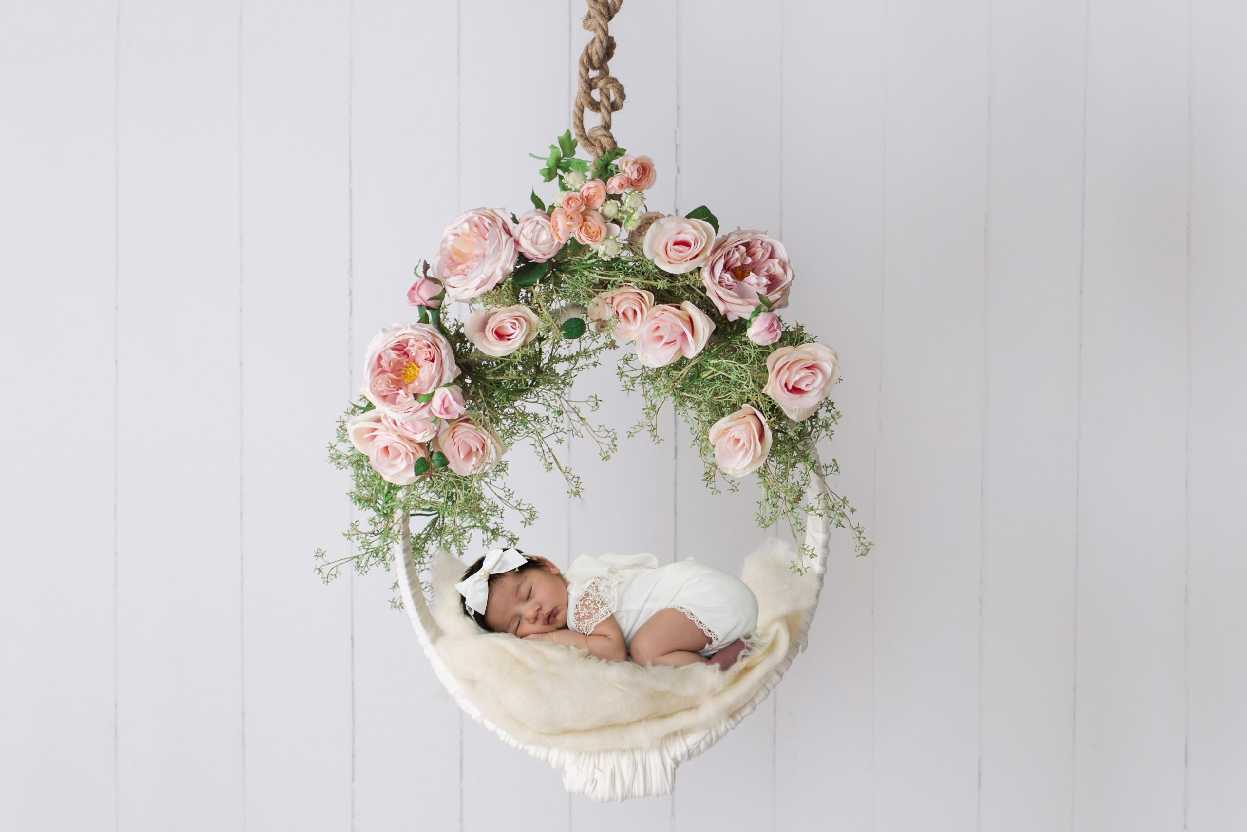Baby sleeping in the swing decorated with roses