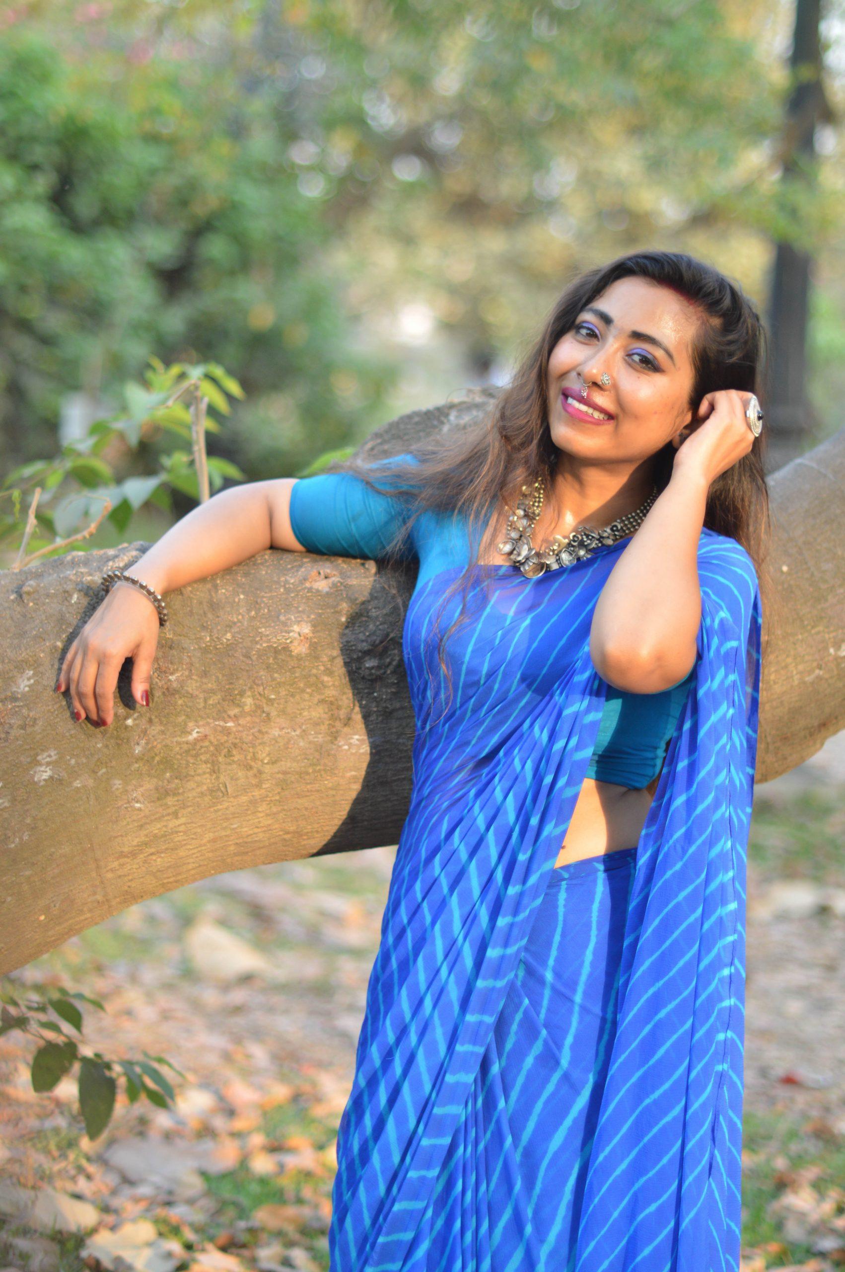 Beautiful girl posing near the tree trunk