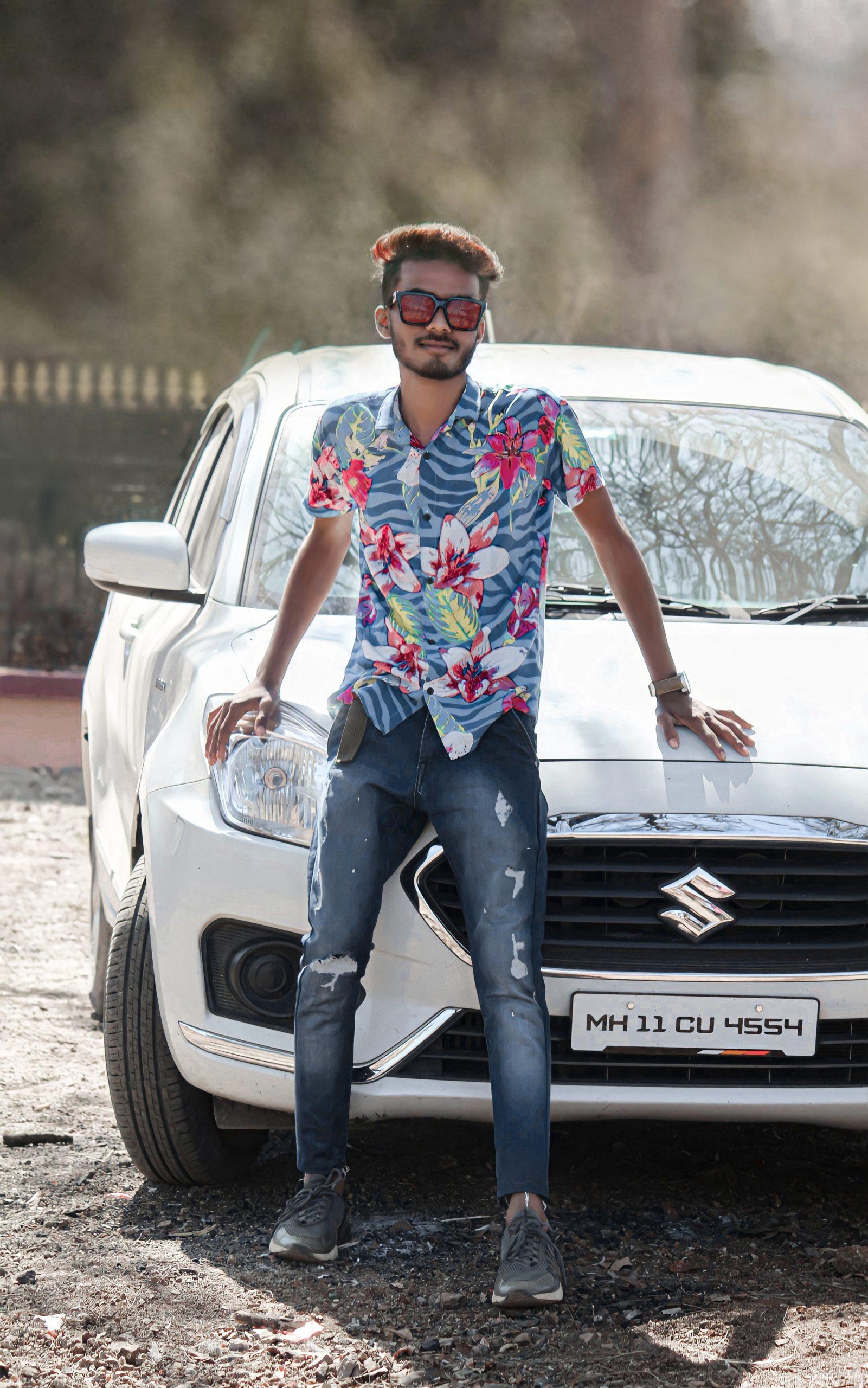 Boy posing in front of car