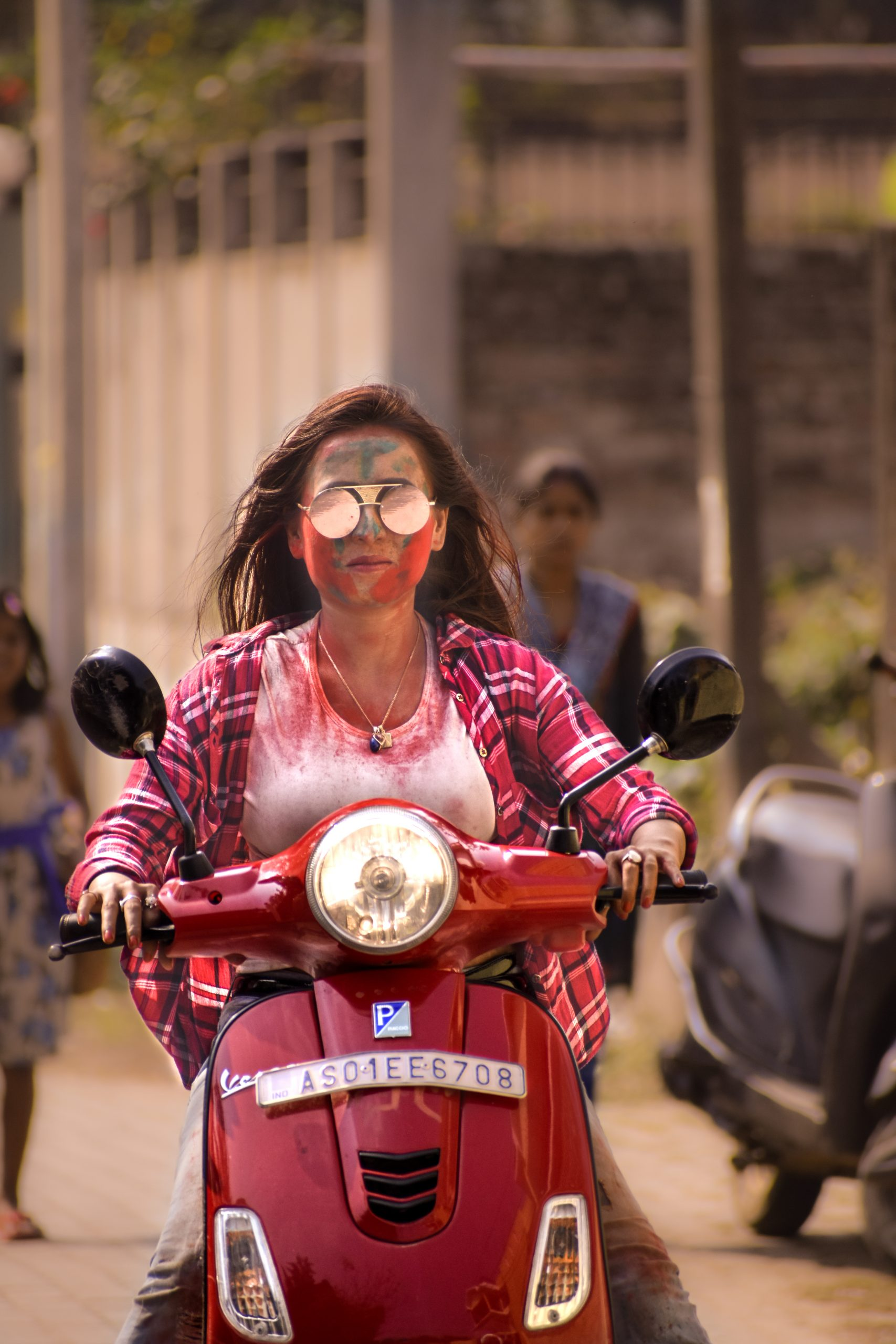 Girl riding scooty during Holi festival