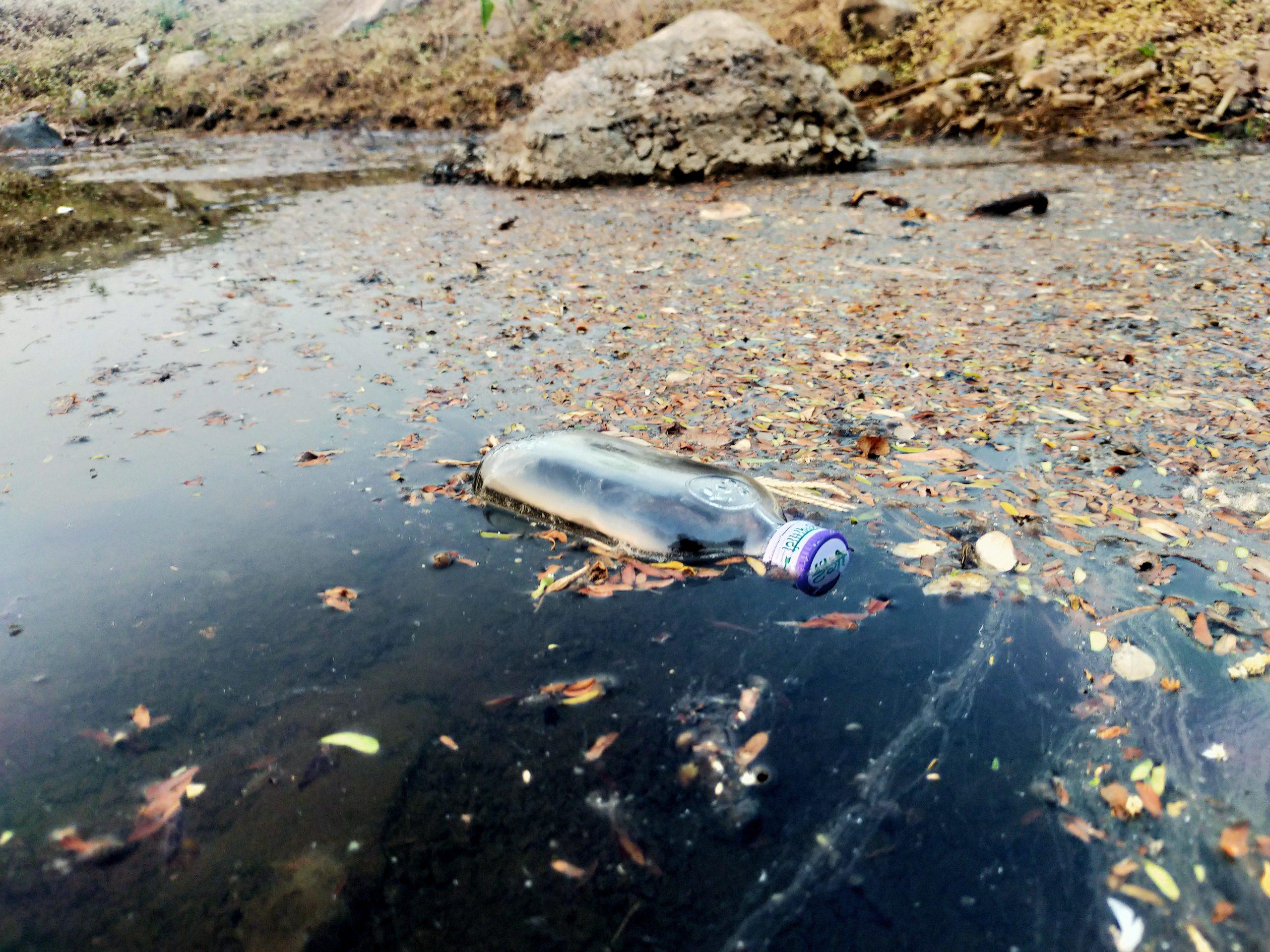 A glass bottle in dirty water