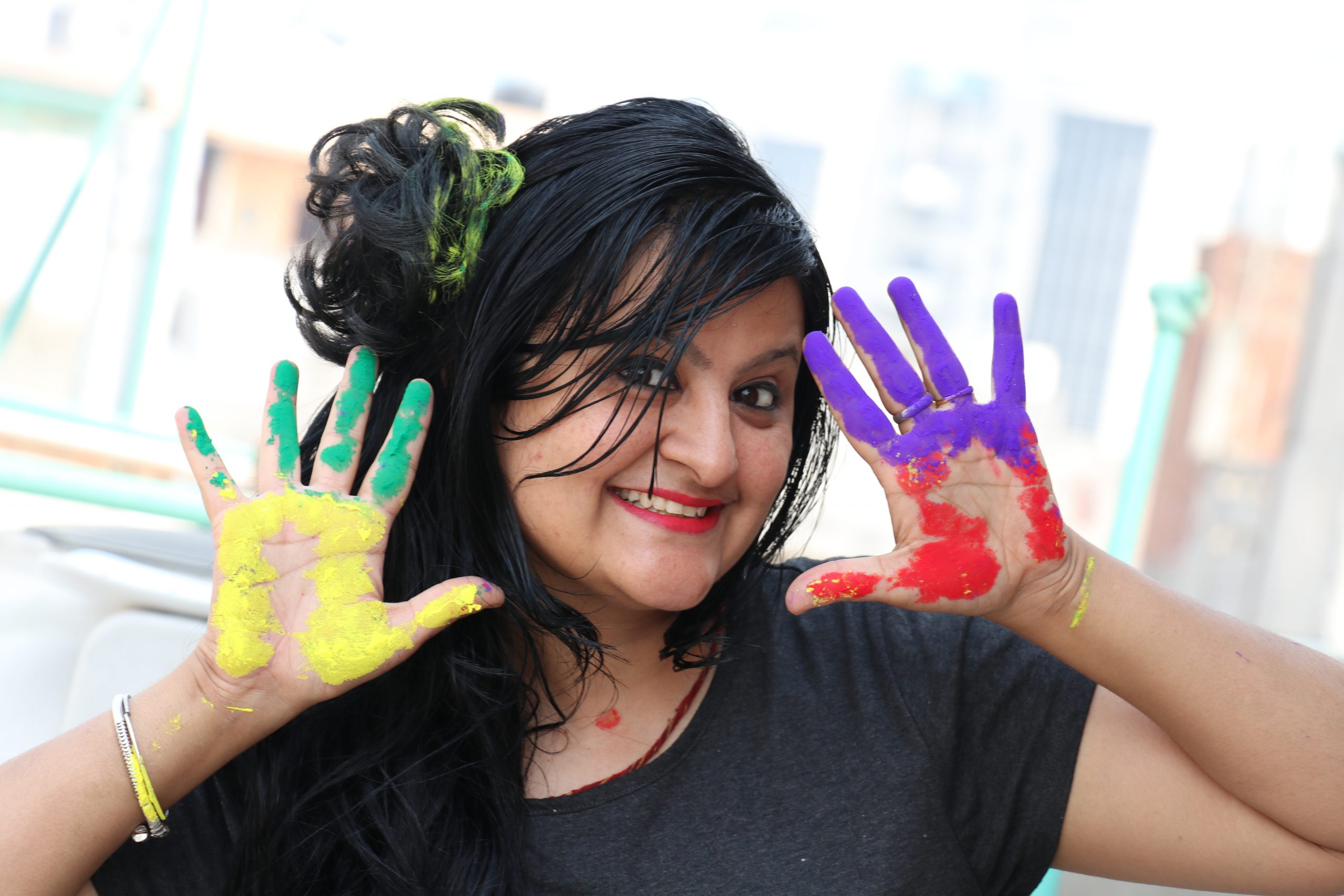 A happy girl showing her colorful hands