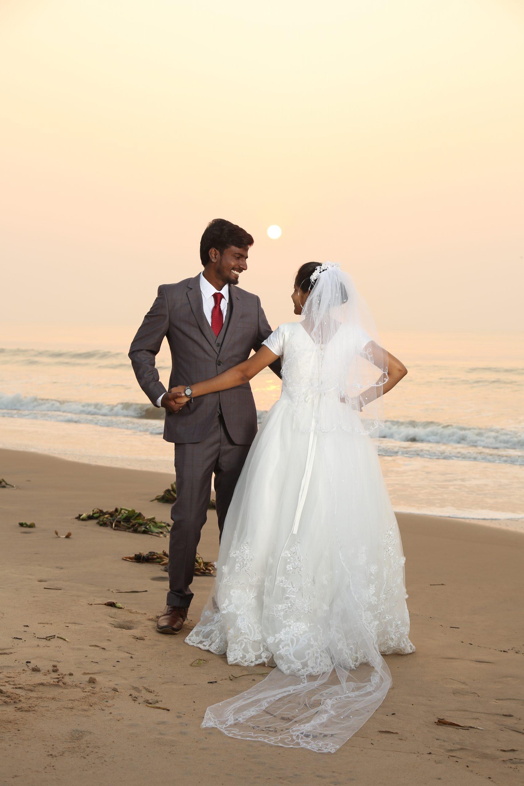 Indian wedding couple posing on the beach