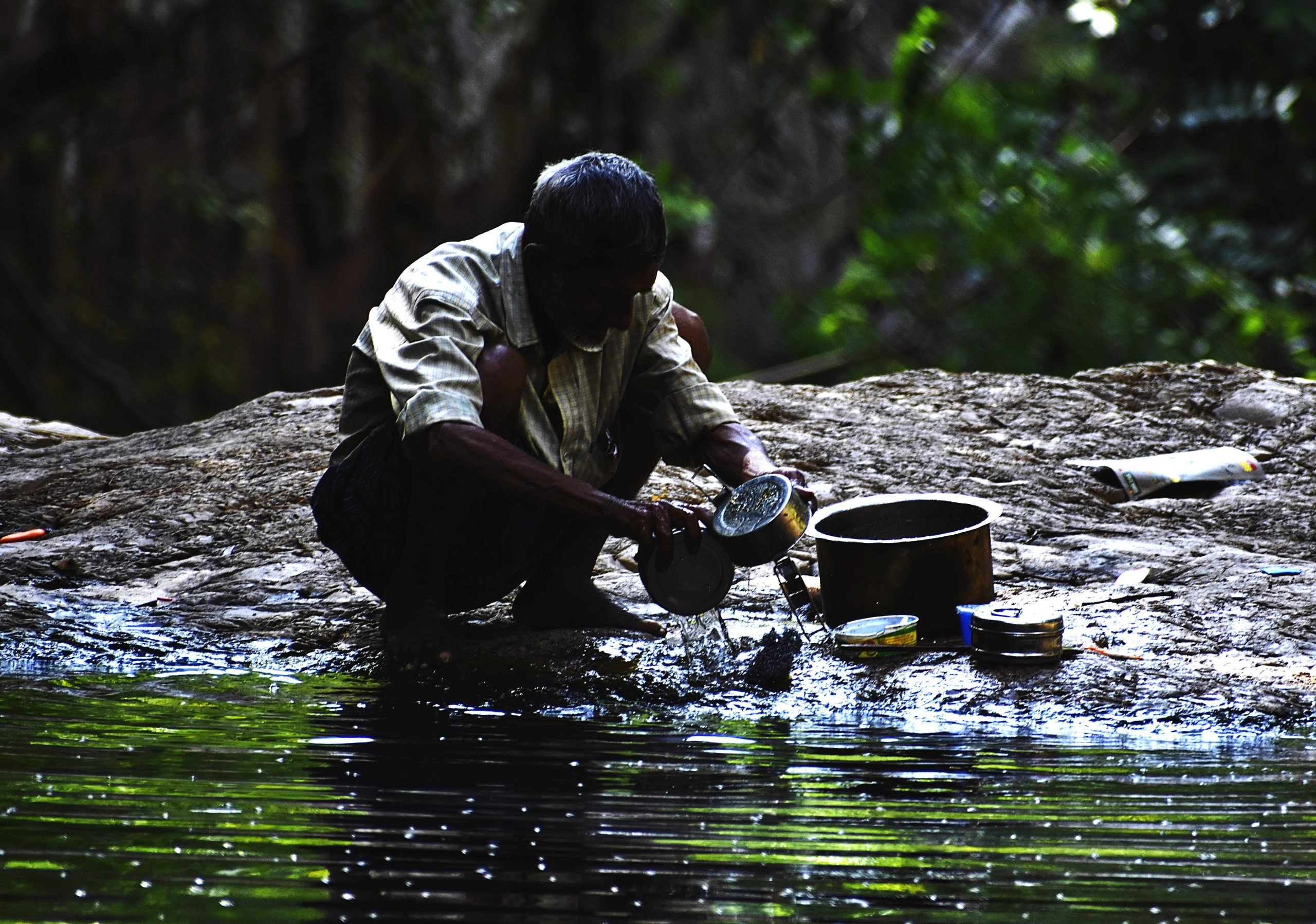 Man cleaning pots near the river