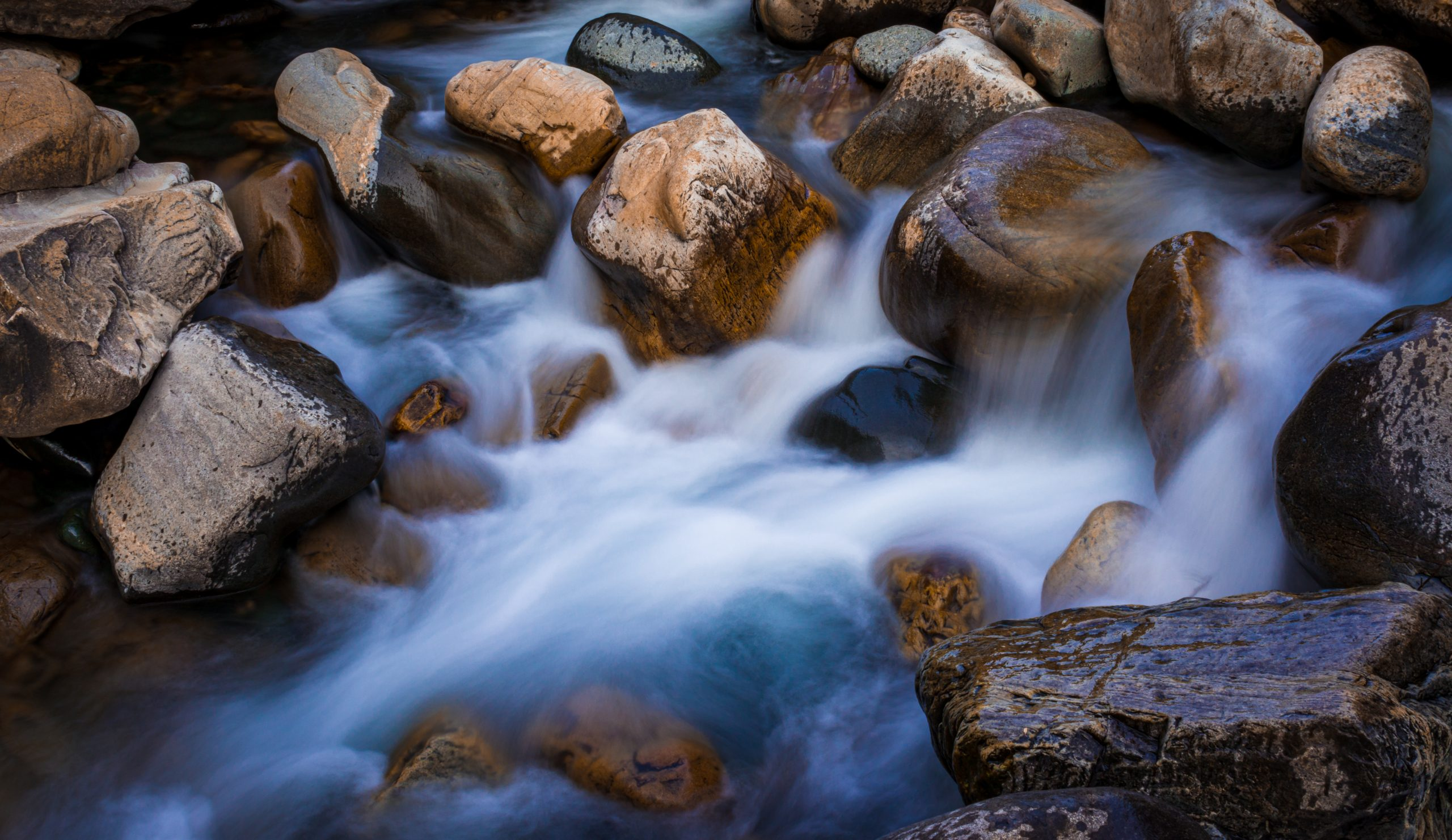 Milky water flowing through stones