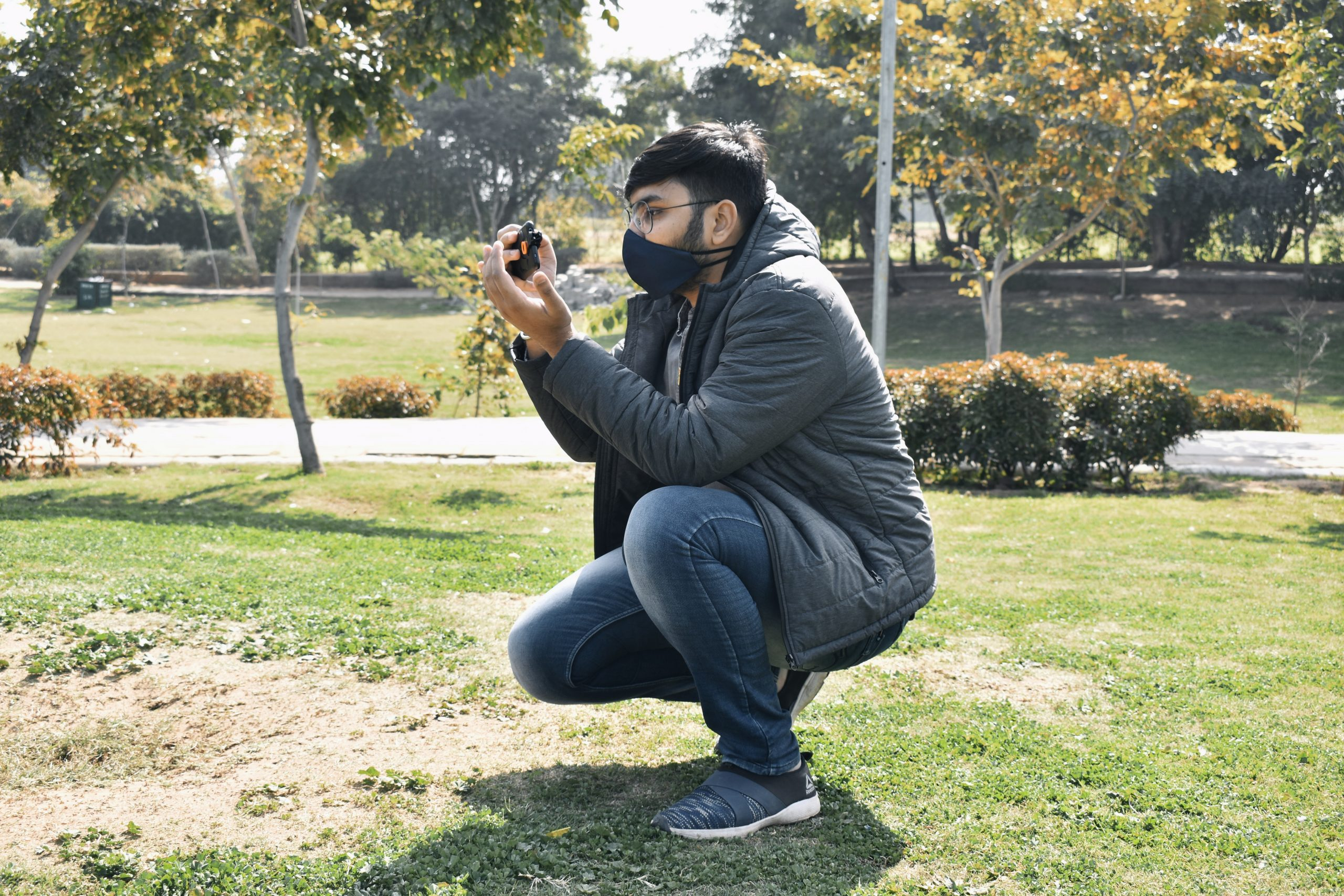 A boy taking a picture in a park