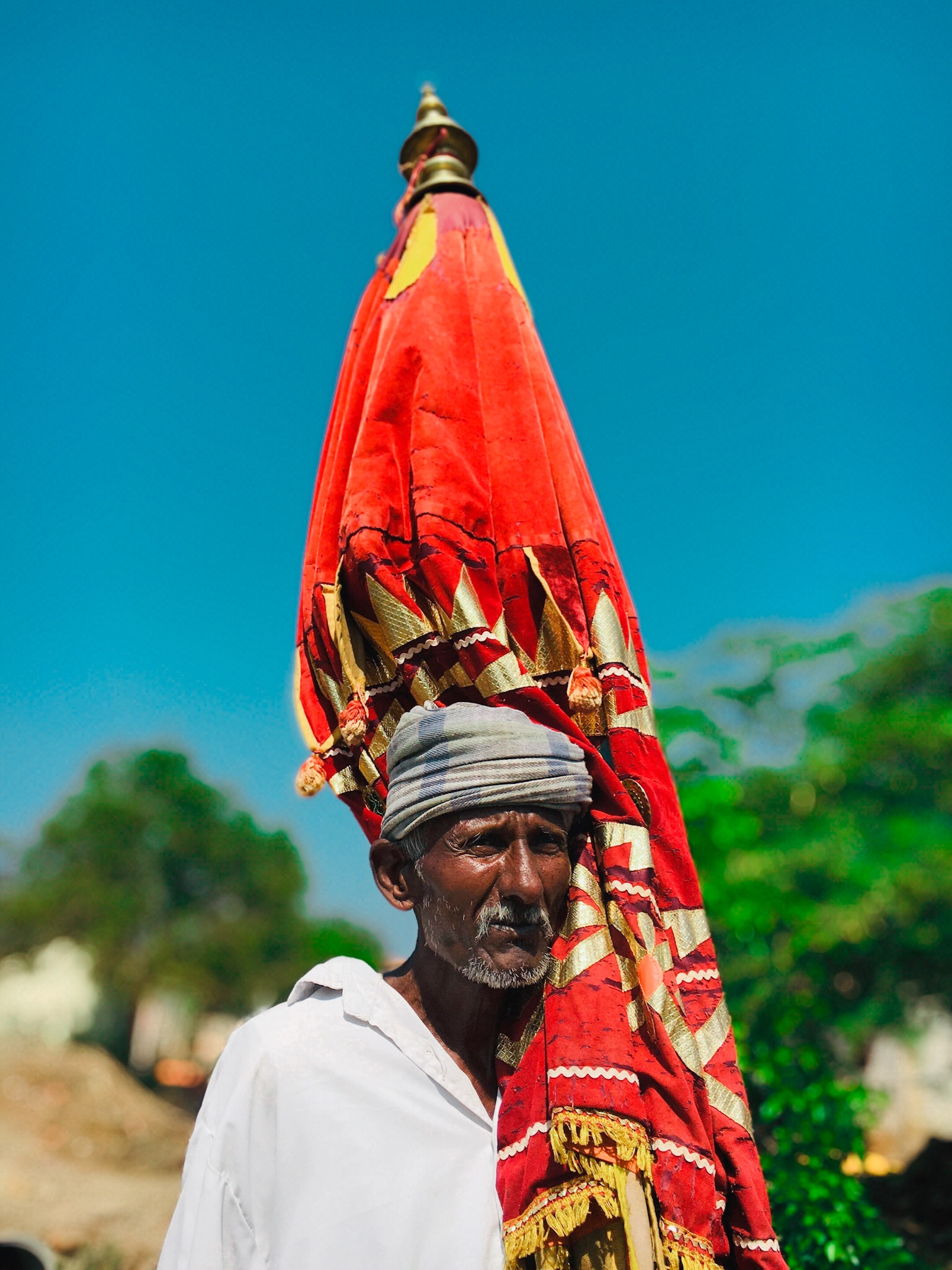 An old man carrying a sacred flag