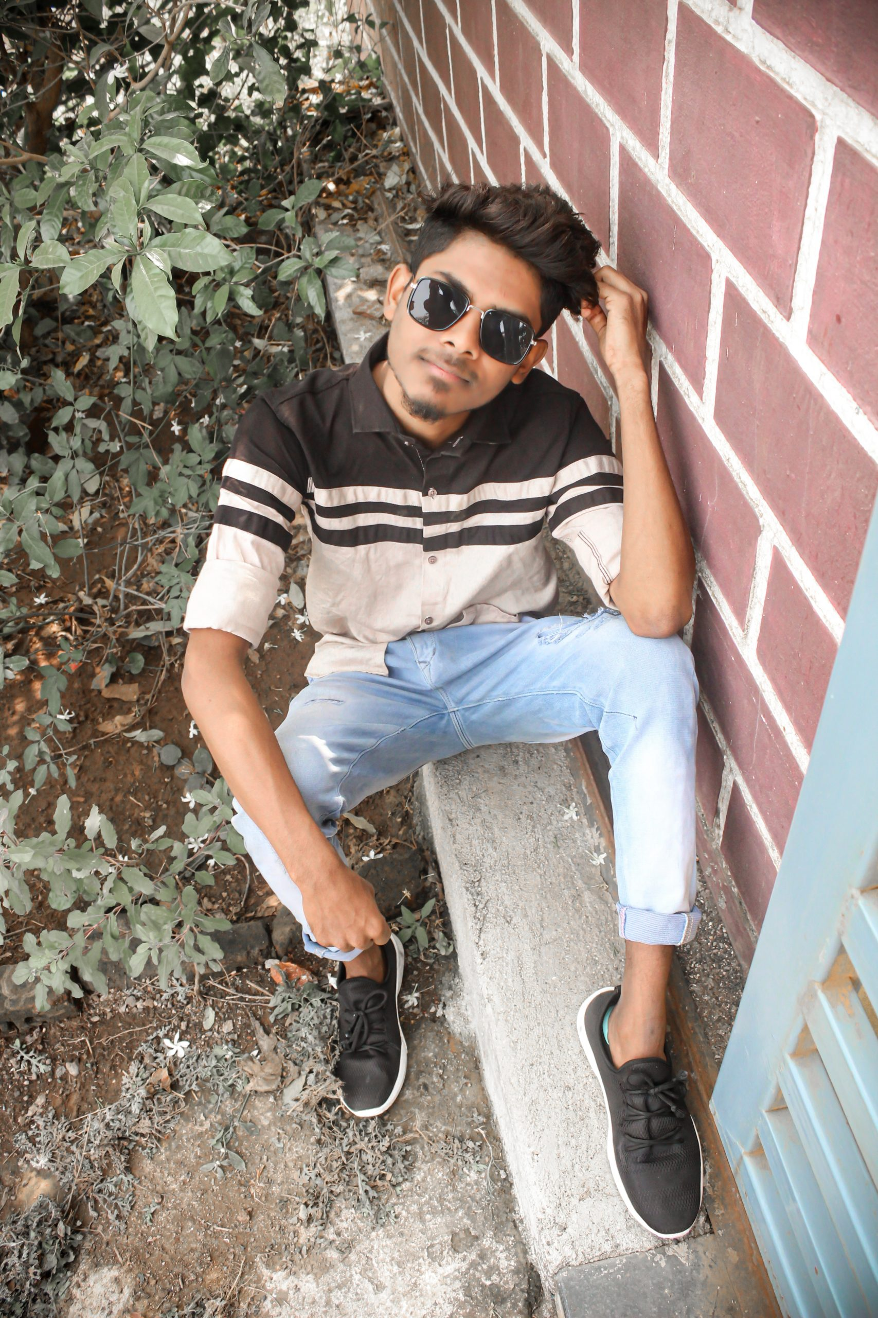 Portrait of a guy sitting on a sidewalk