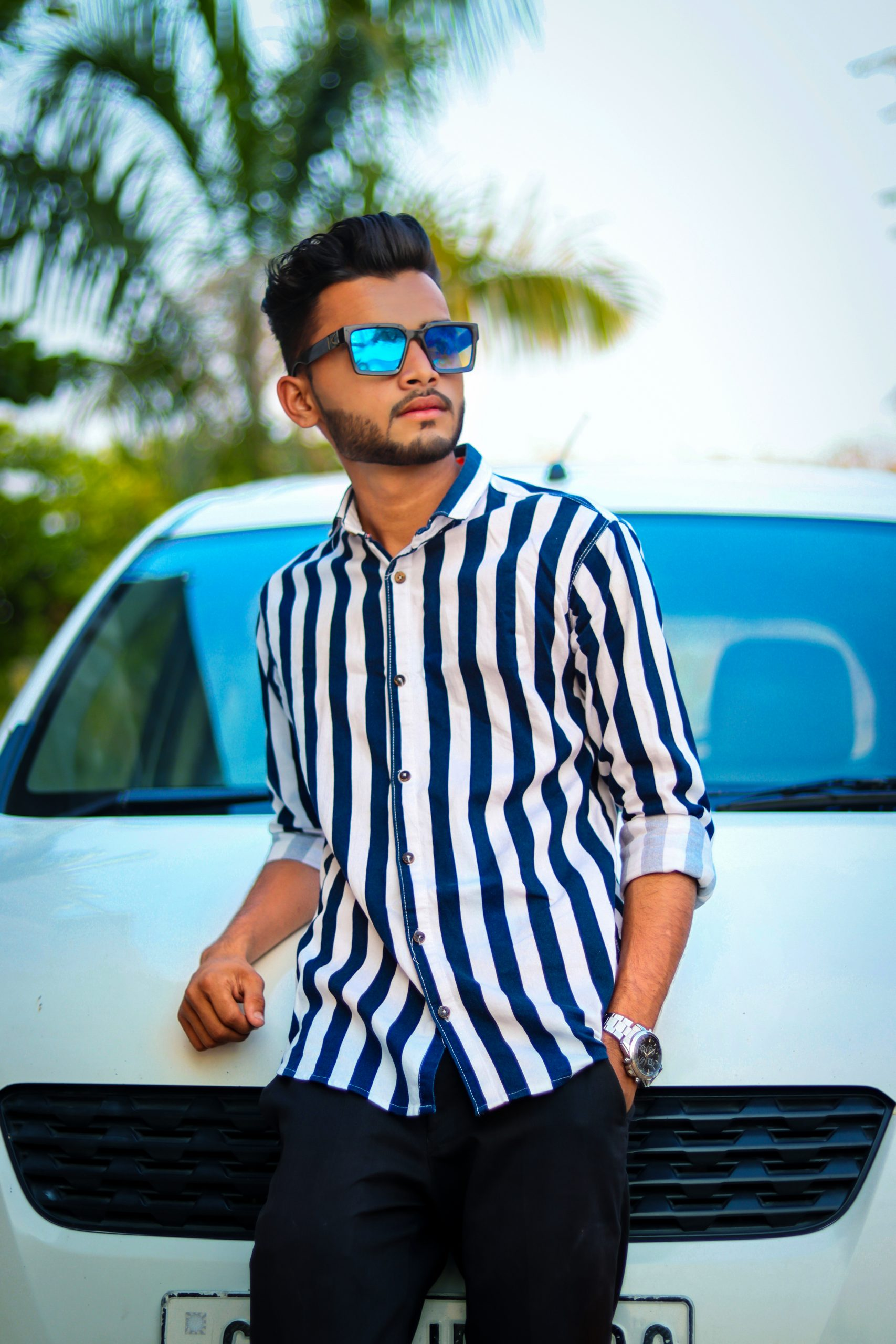 Stylish boy posing in front of car