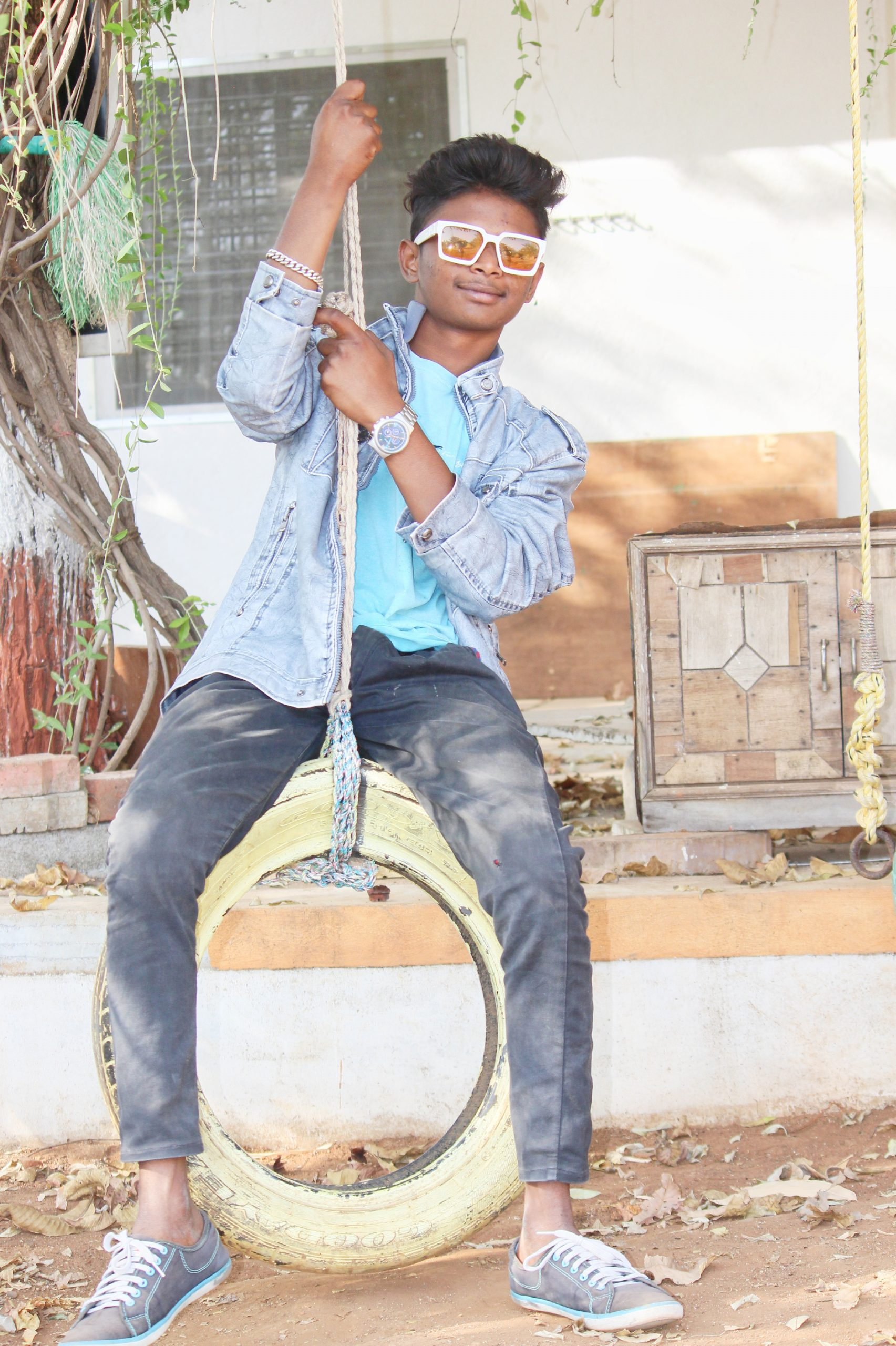 Stylish boy posing on the tyre swing