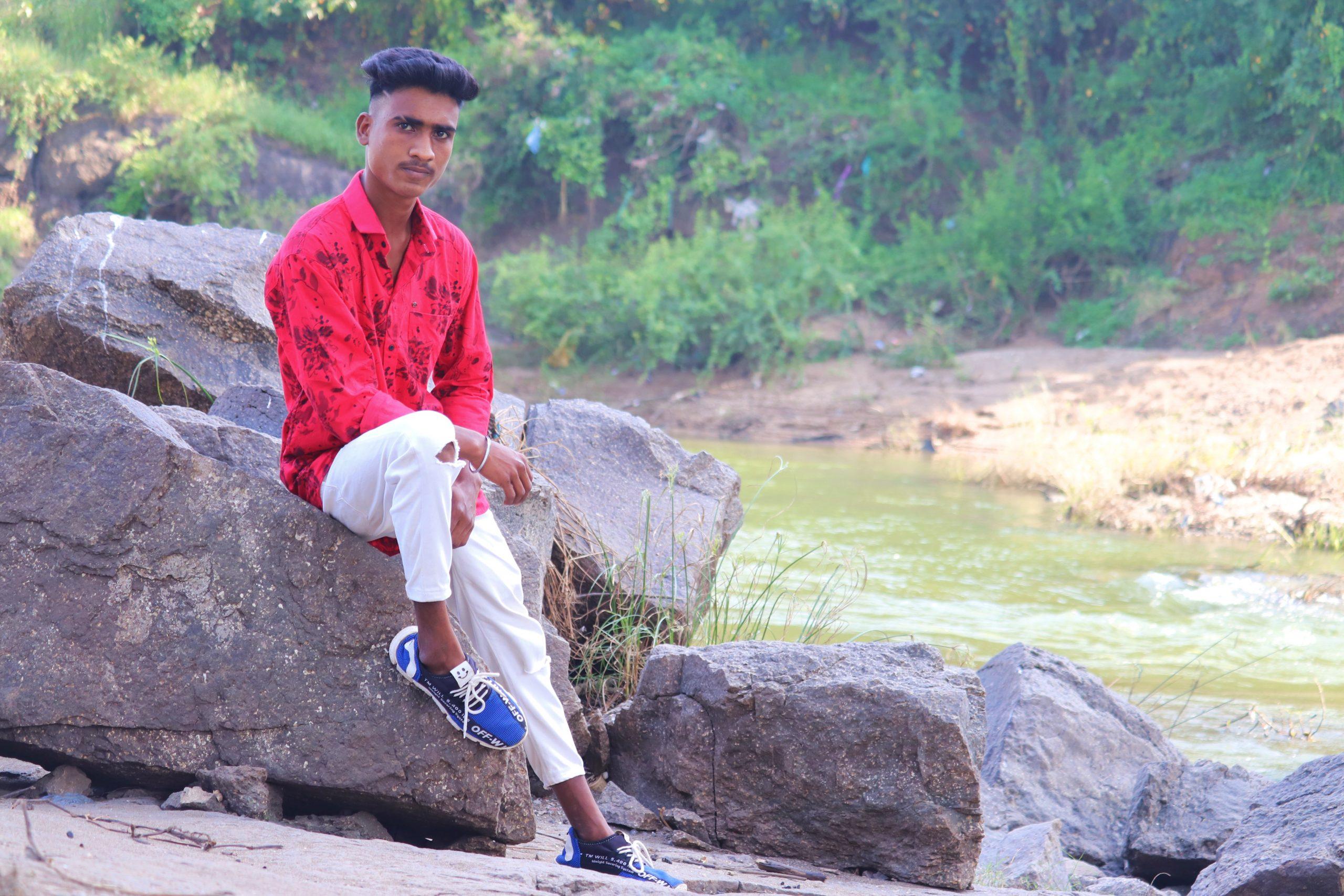 Stylish boy posing while sitting on rock