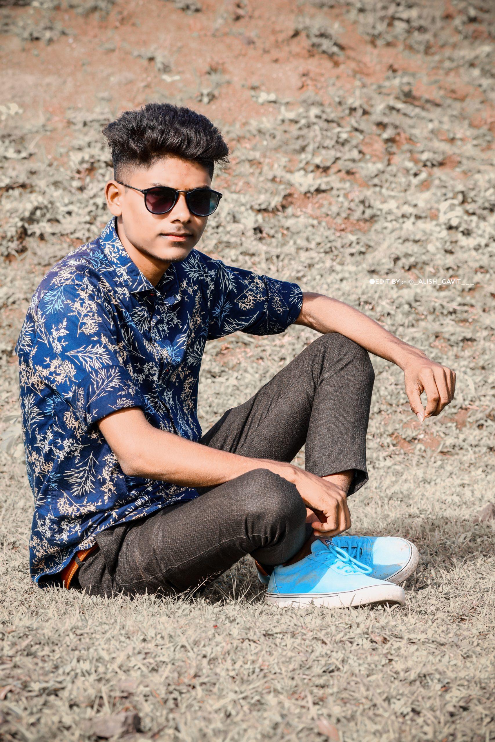 Stylish boy sitting on the floor and posing