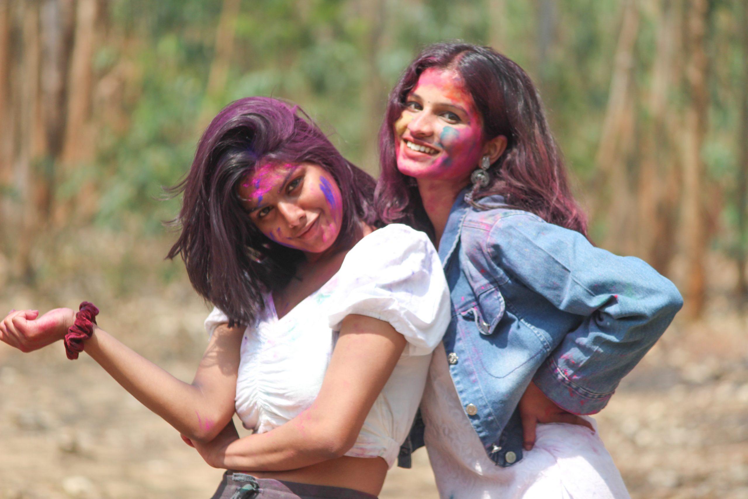 Stylish girls posing with Holi colors