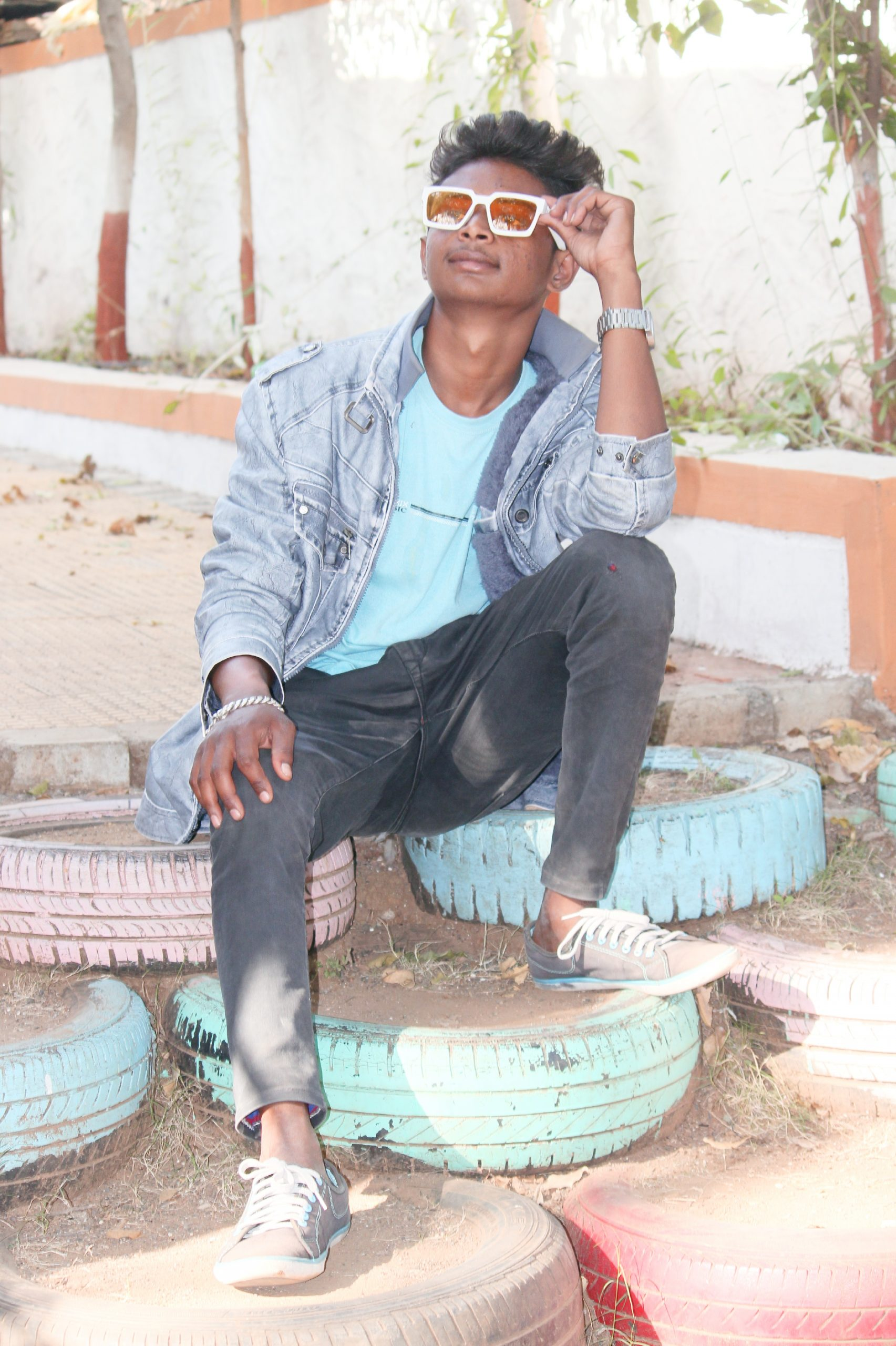 Young boy posing while sitting on the tyres