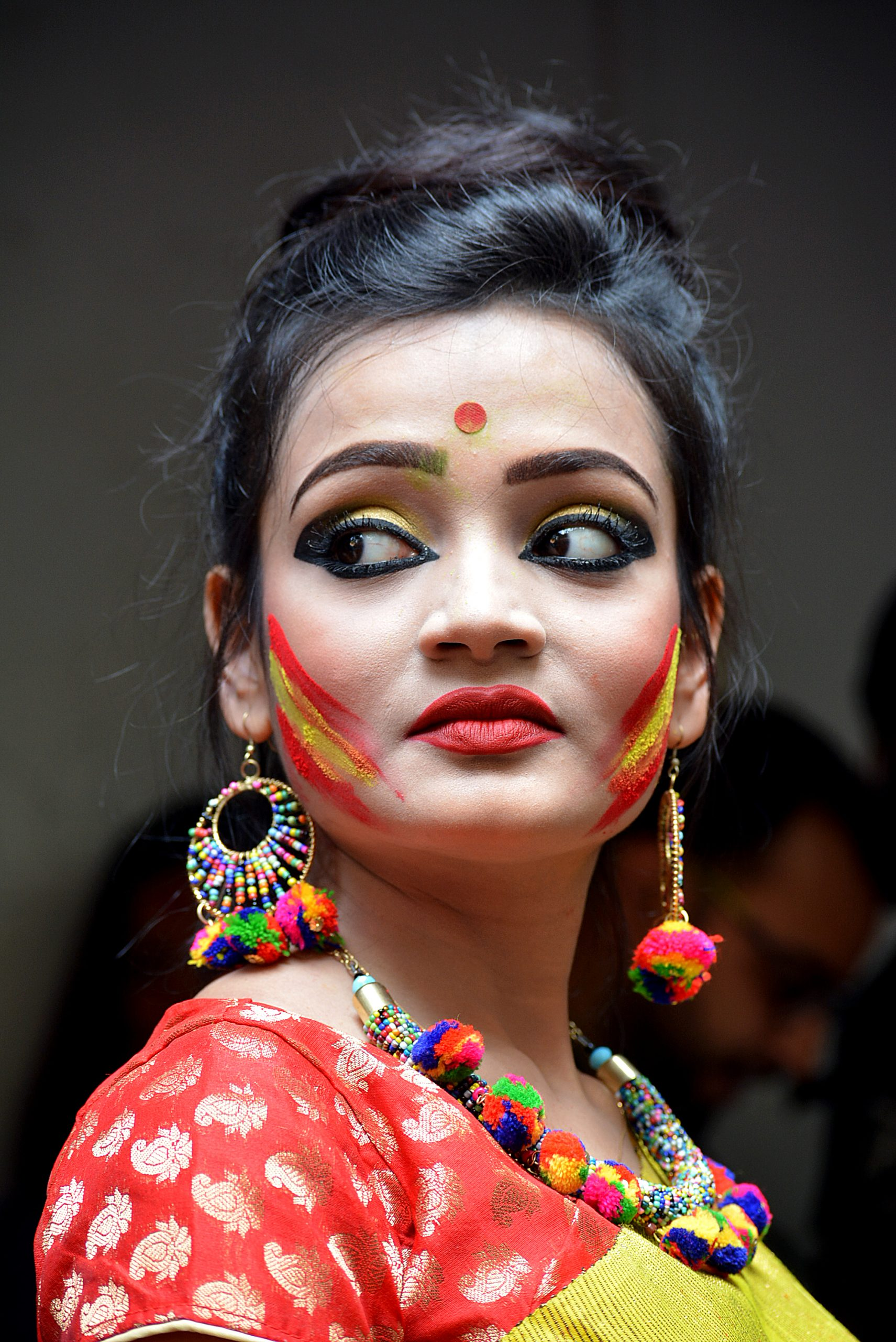 A fashion model with Holi colors on face