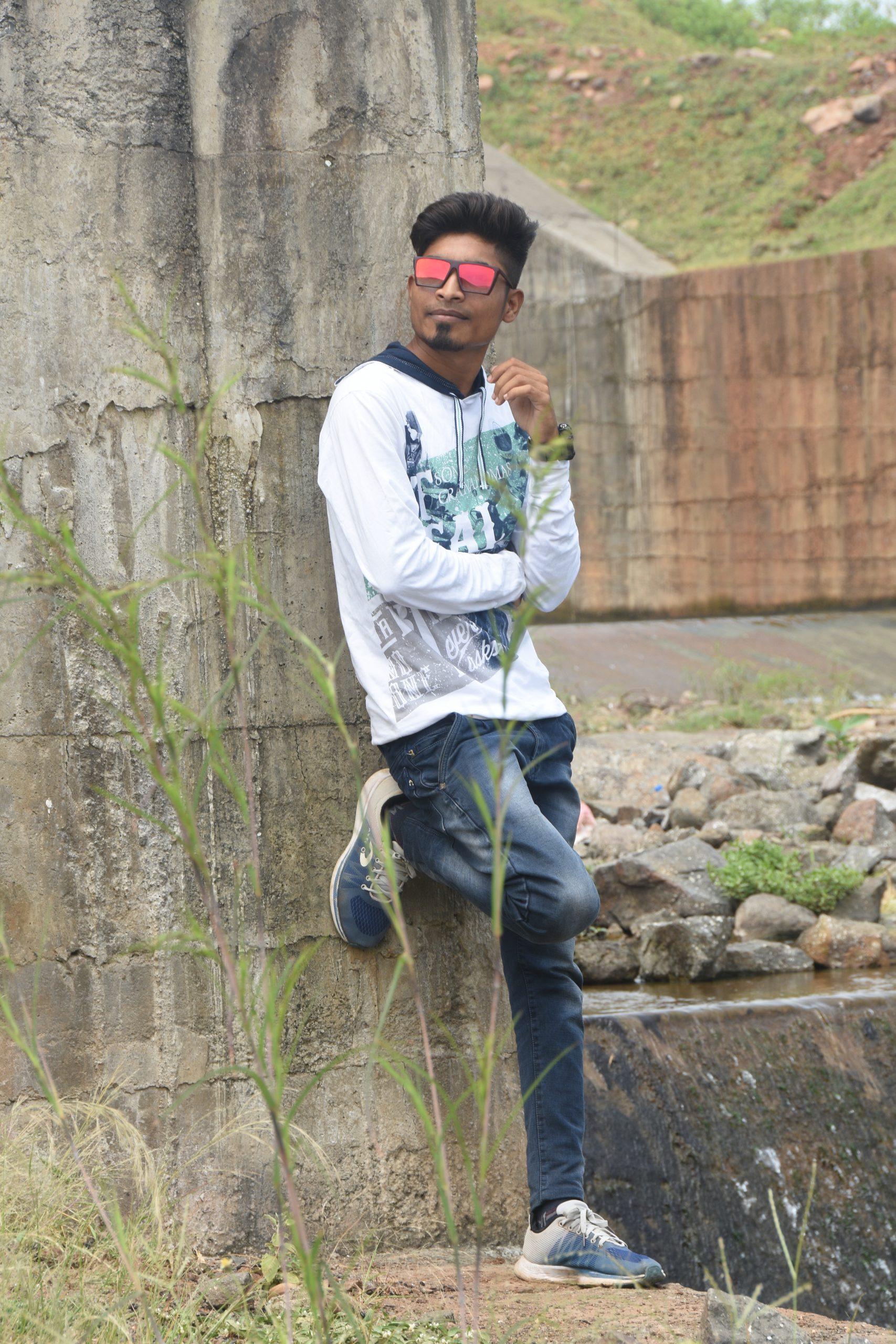 A stylish boy posing against the wall