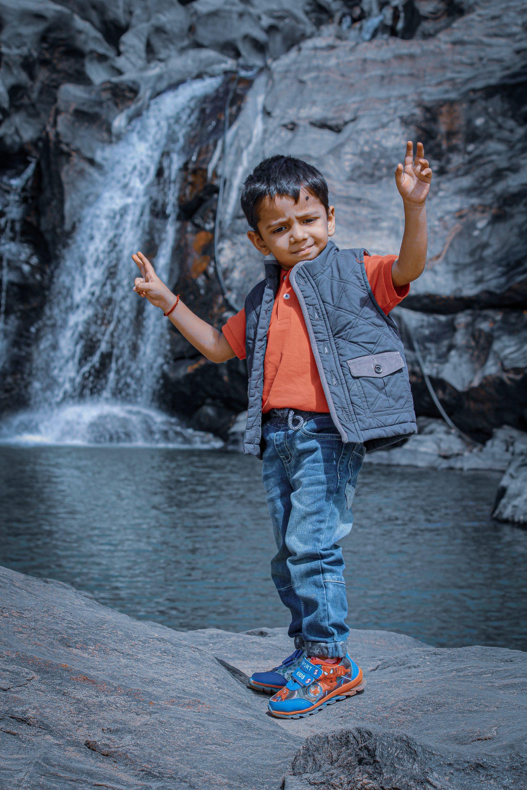 A stylish kid dancing near a waterfall