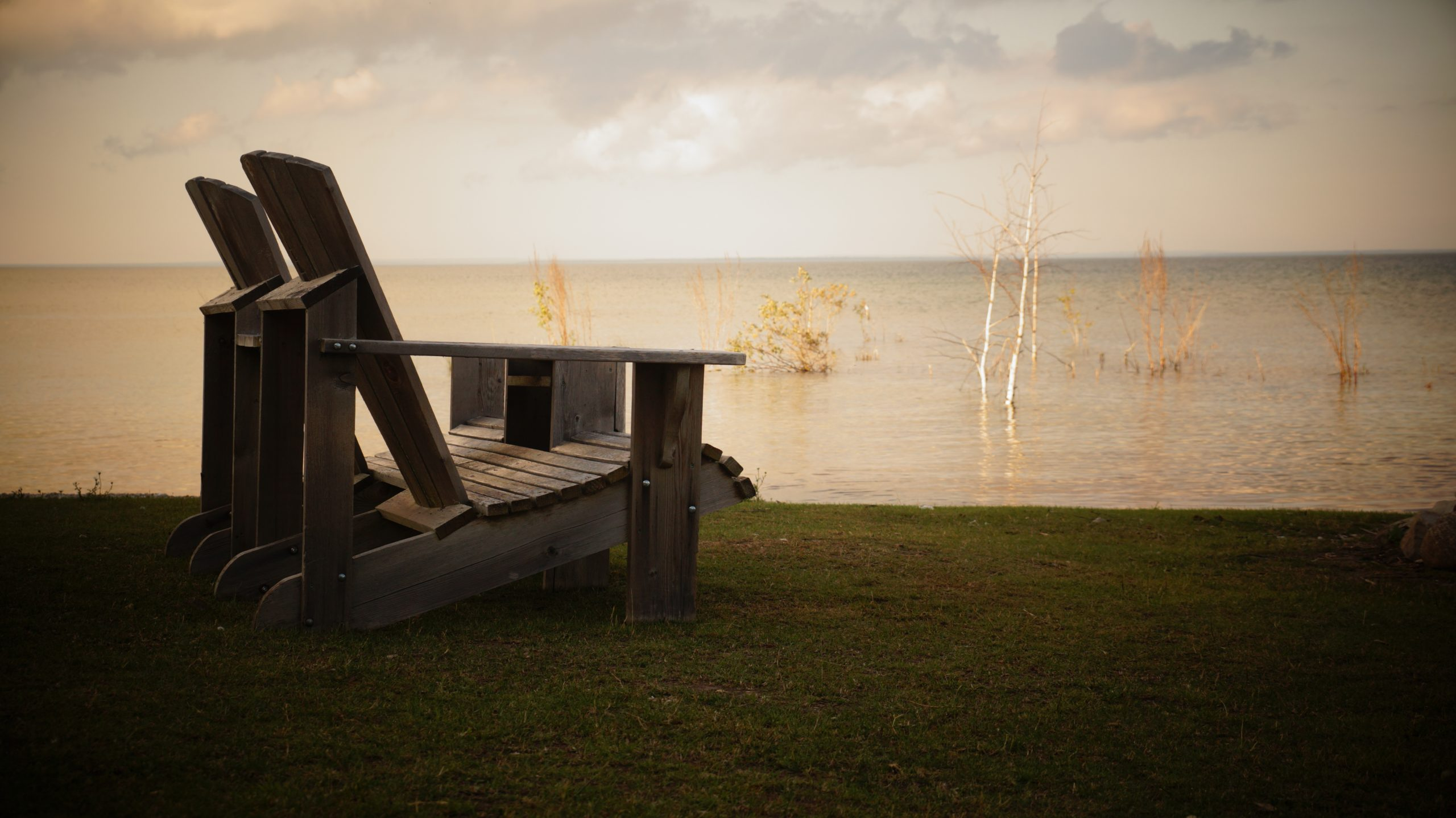 A wooden chair near a lake