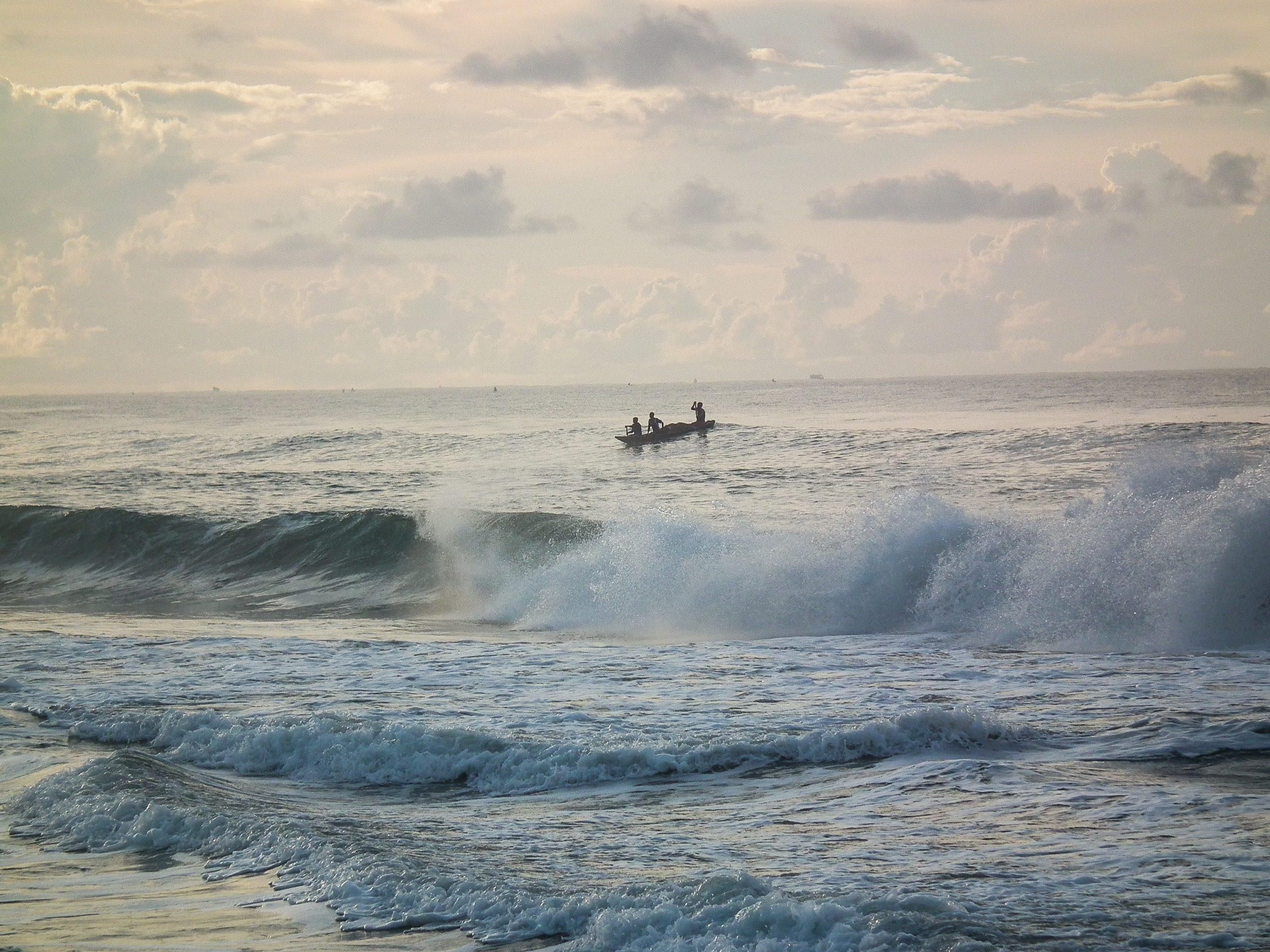 A boat floating along sea waves