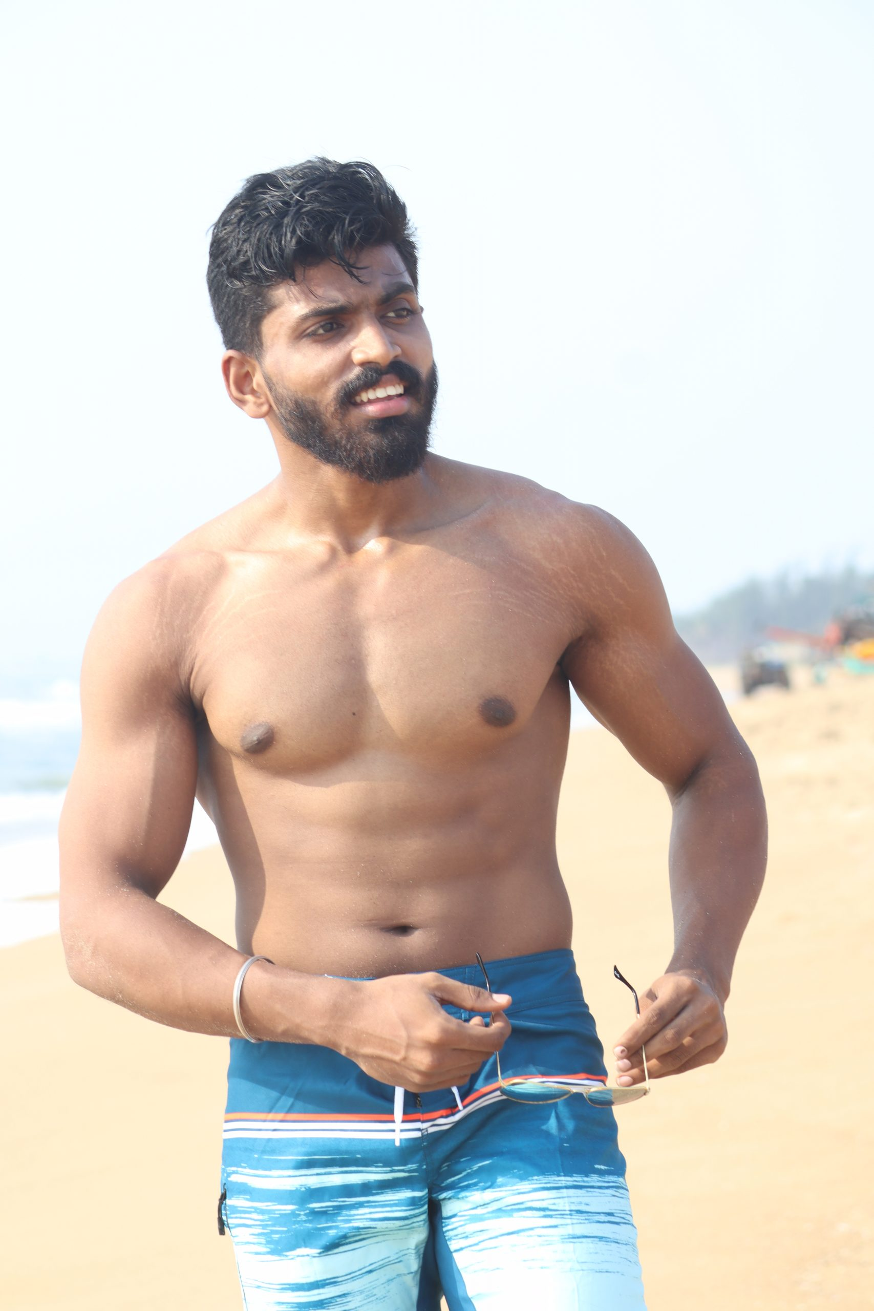 Boy showing his arms and muscles on the beach
