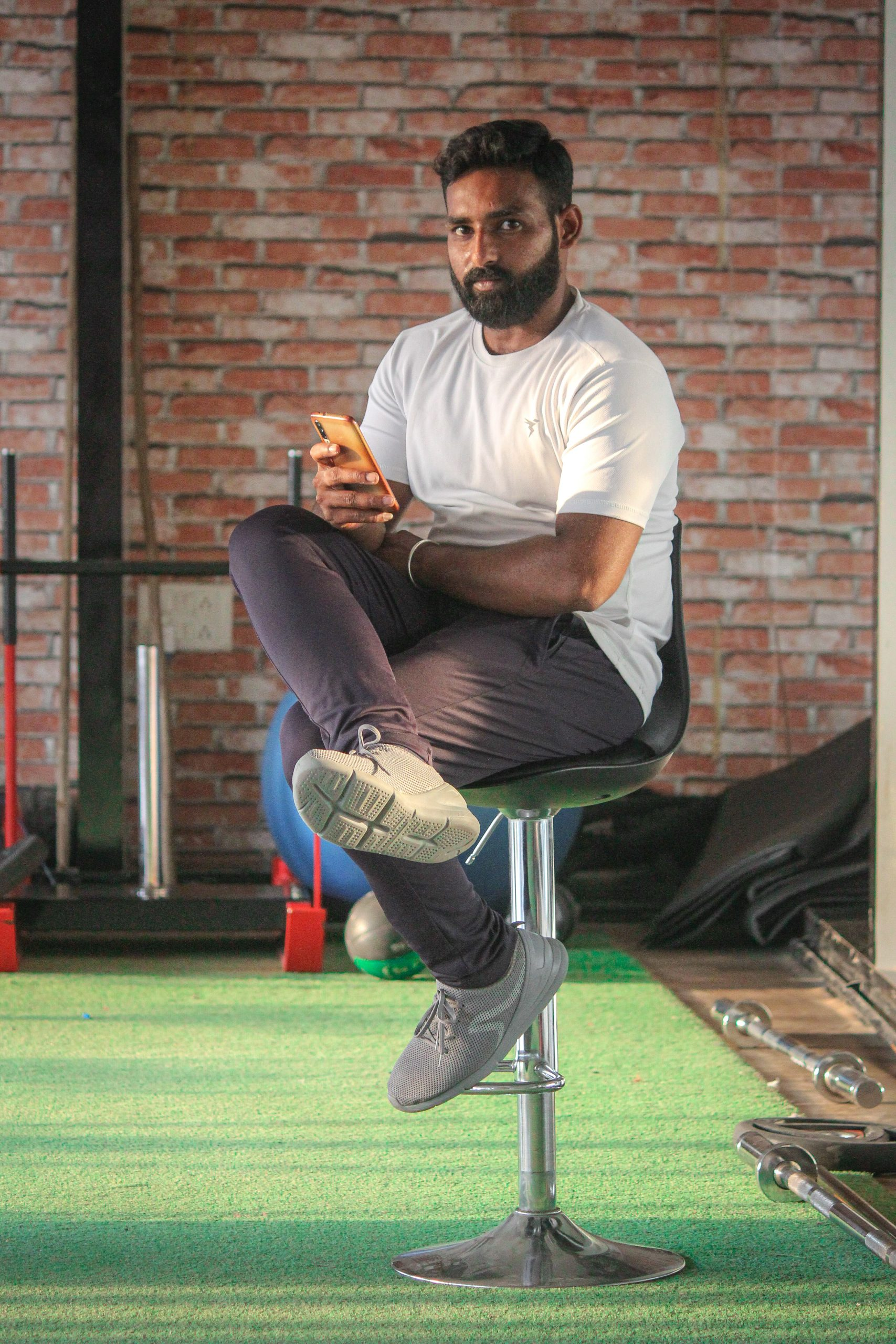 Boy sitting on the chair and posing in the gym
