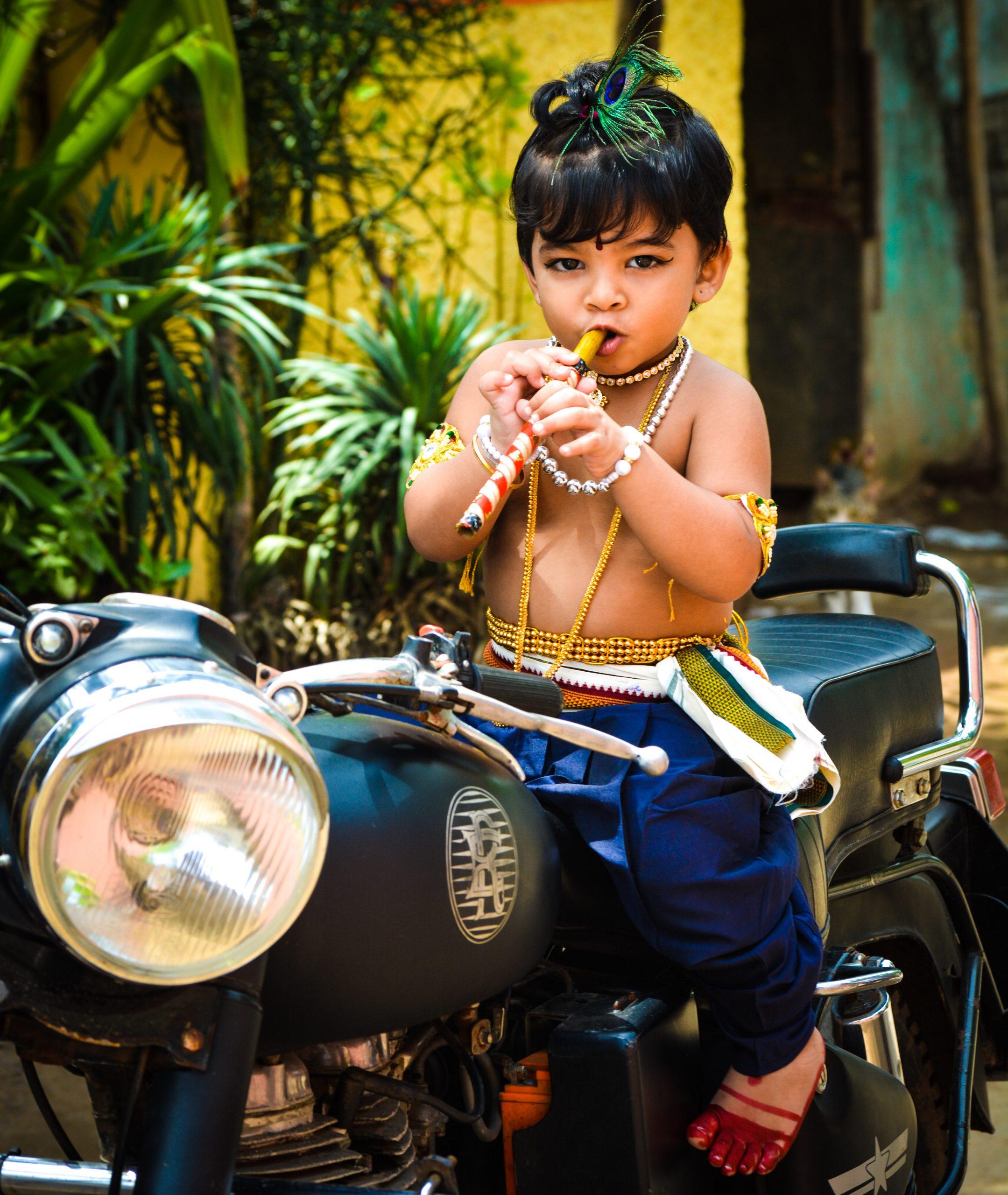 Little baby in Krishna Avtar on Royal Enfield bike