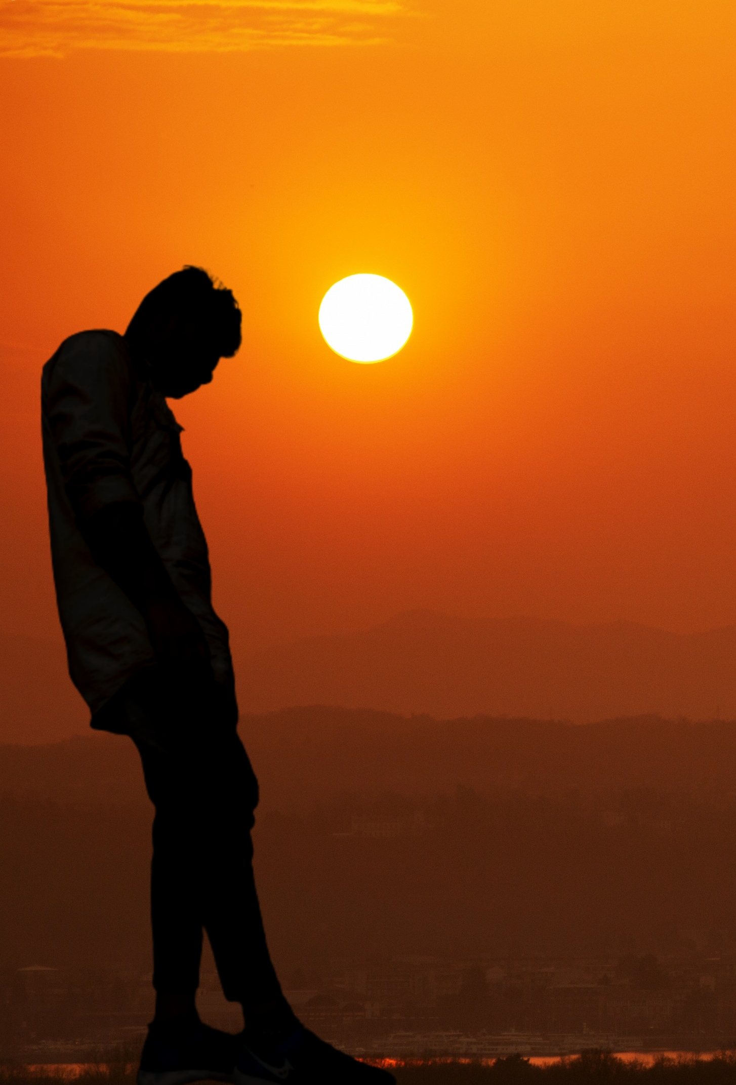Boy standing under orange Sunlight
