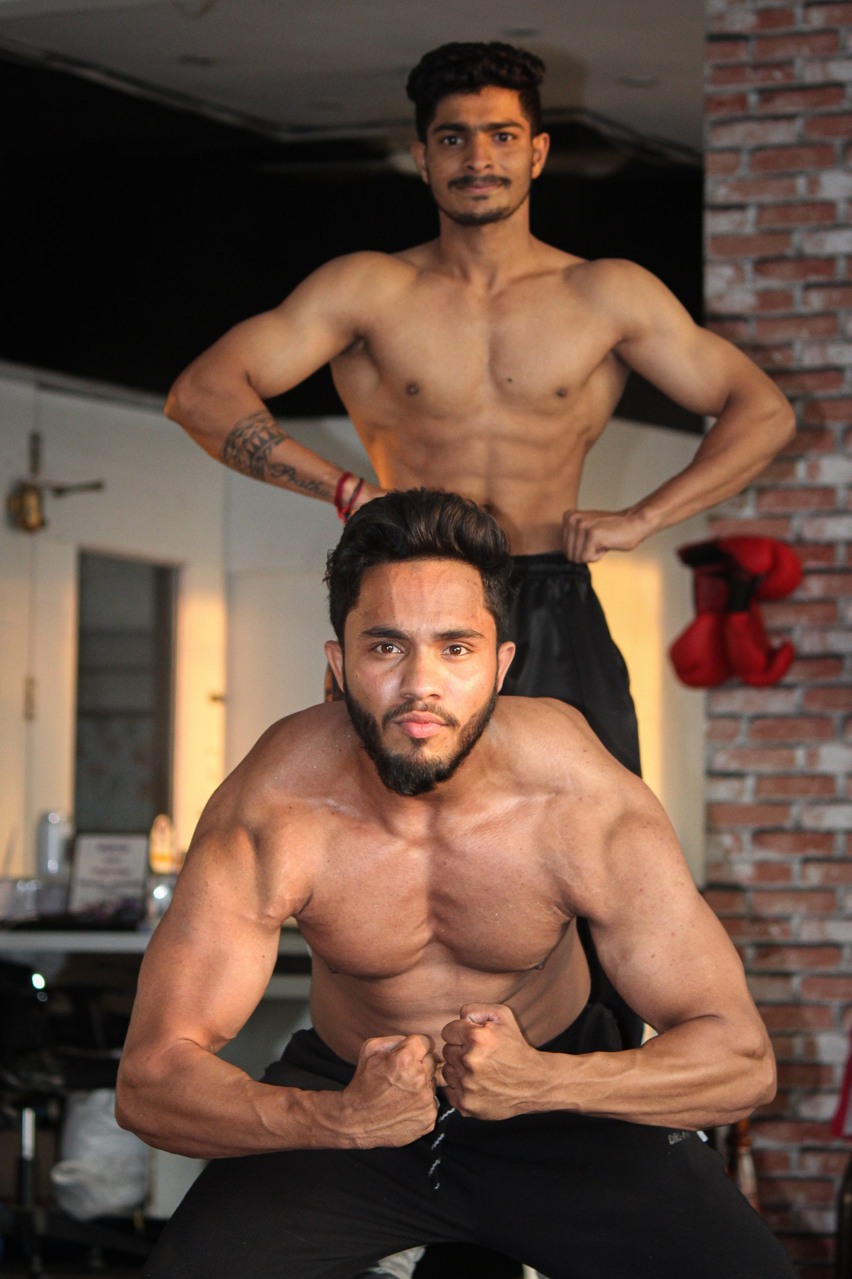 Two fitness models posing in the gym
