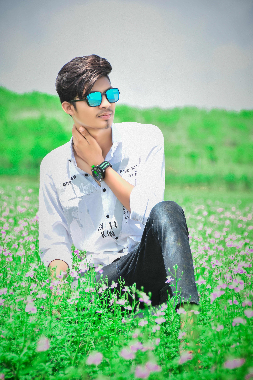 Stylish boy posing in the grassy farm