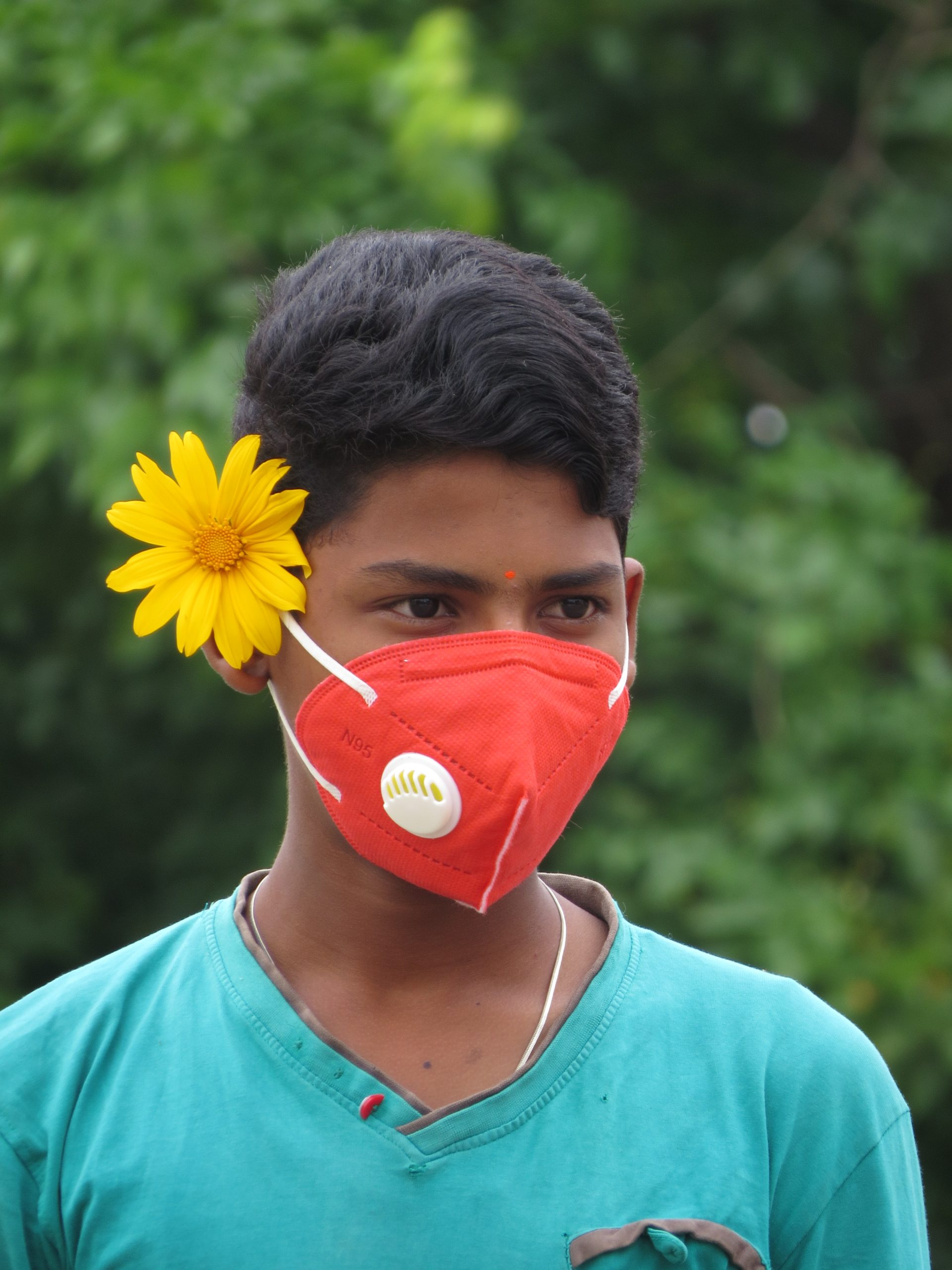 A boy with face cover and a flower