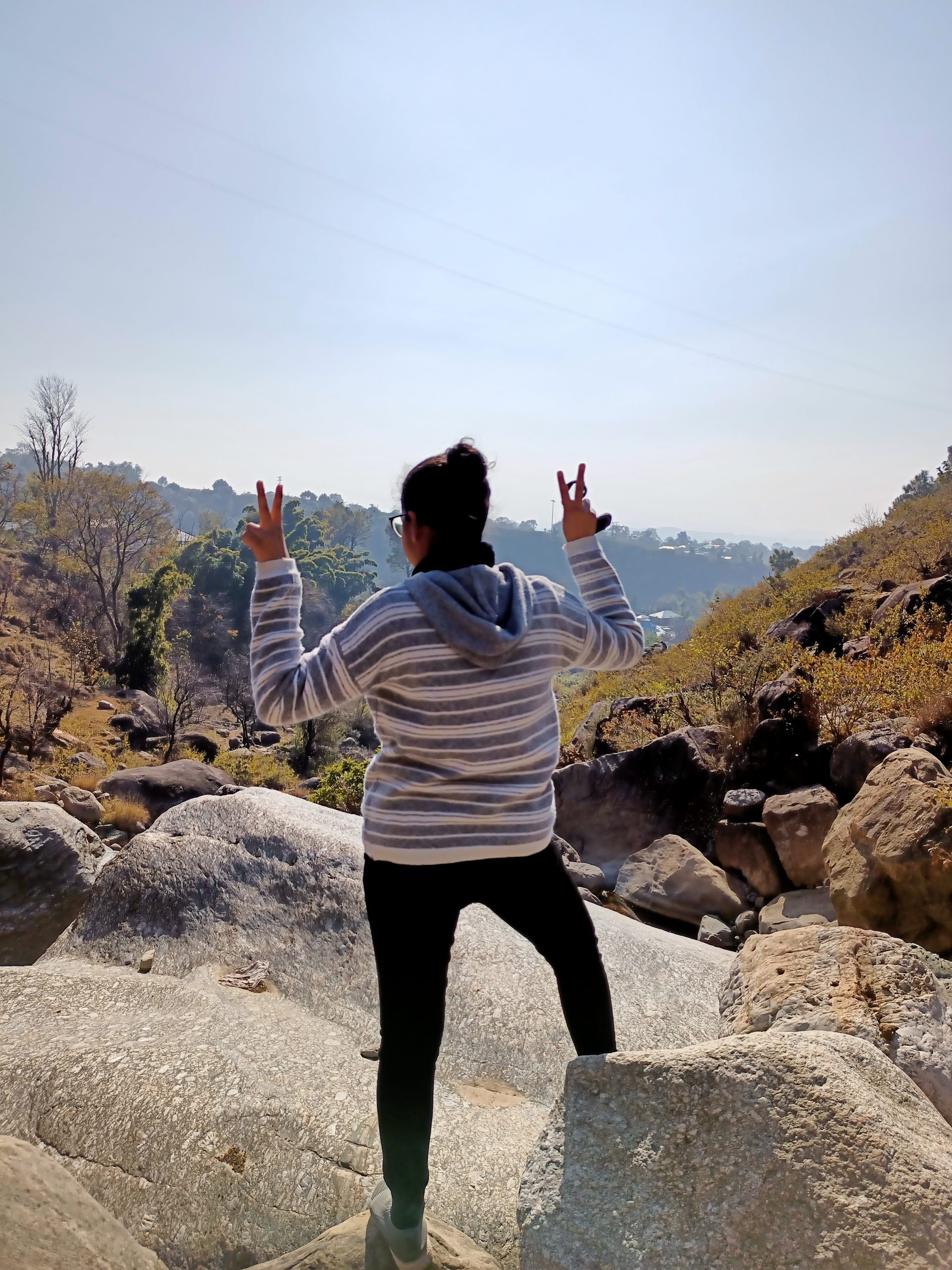 A girl showing victory sign on a rock