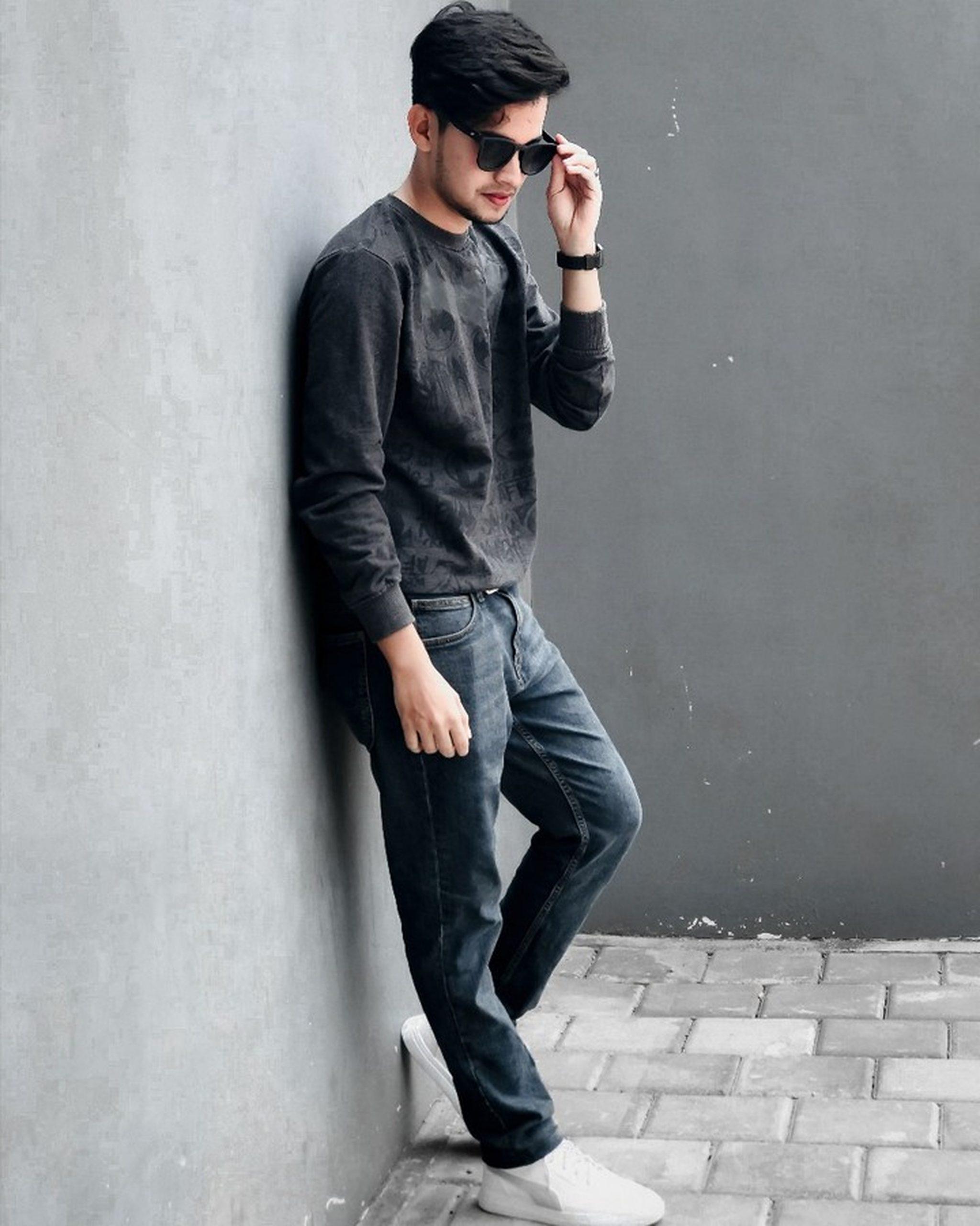 A stylish boy standing against a wall