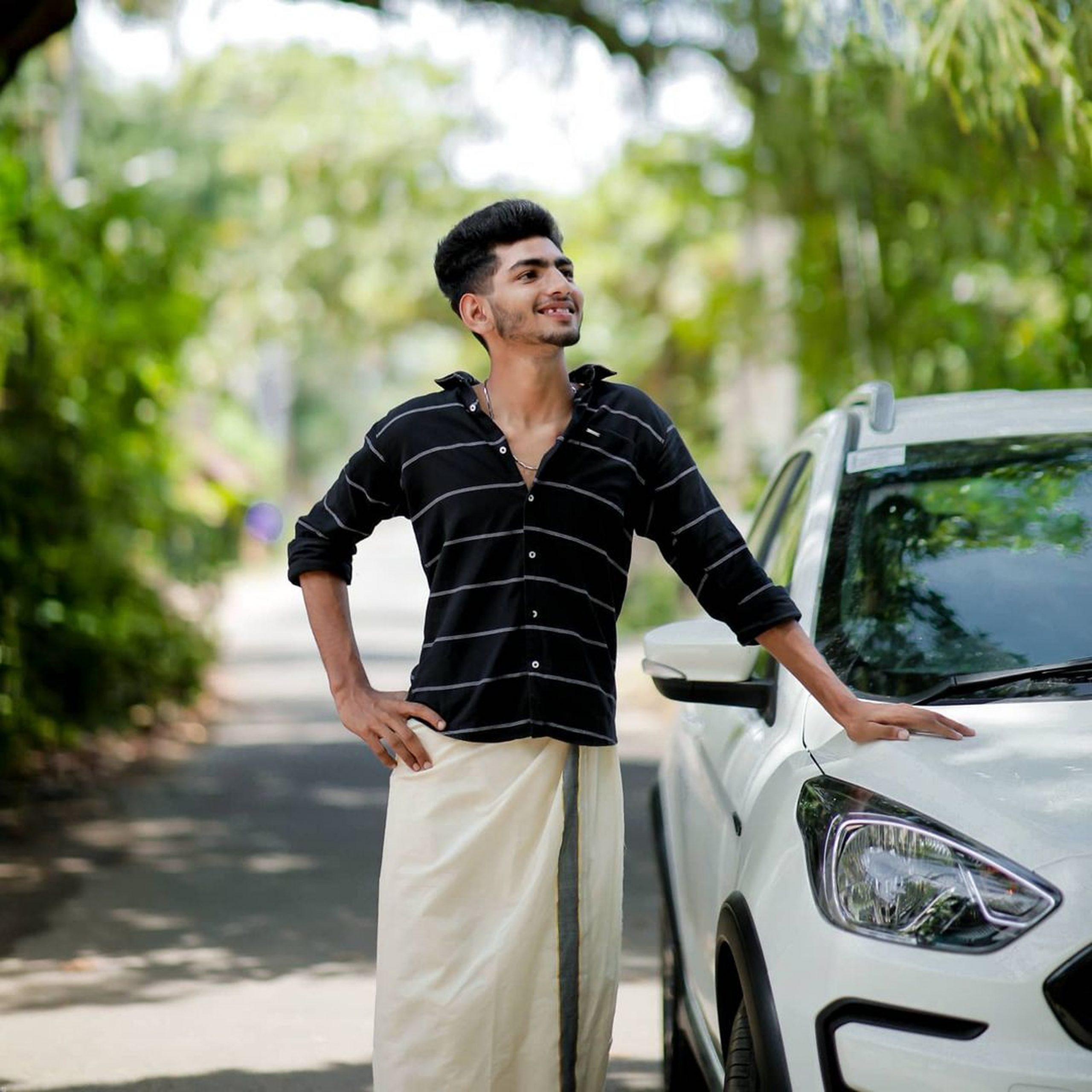 Model wearing lungi and posing near the car