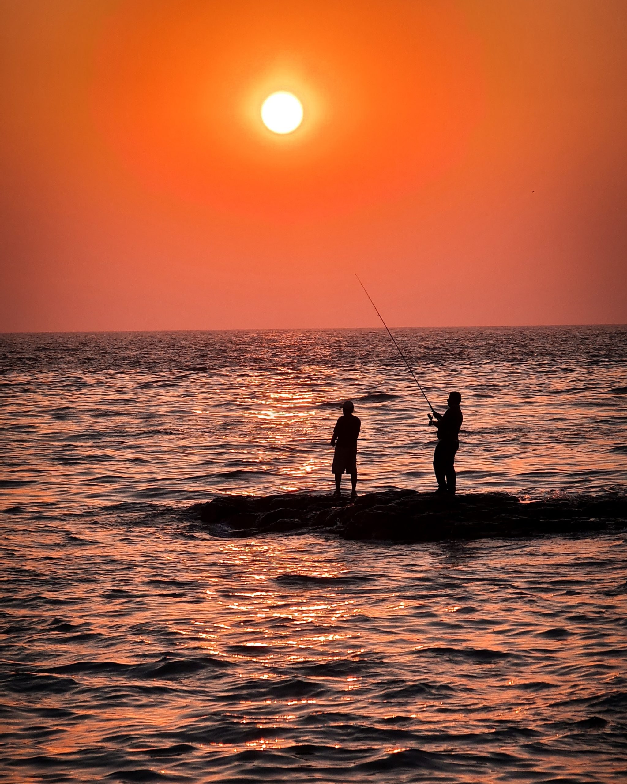 People fishing during sunset