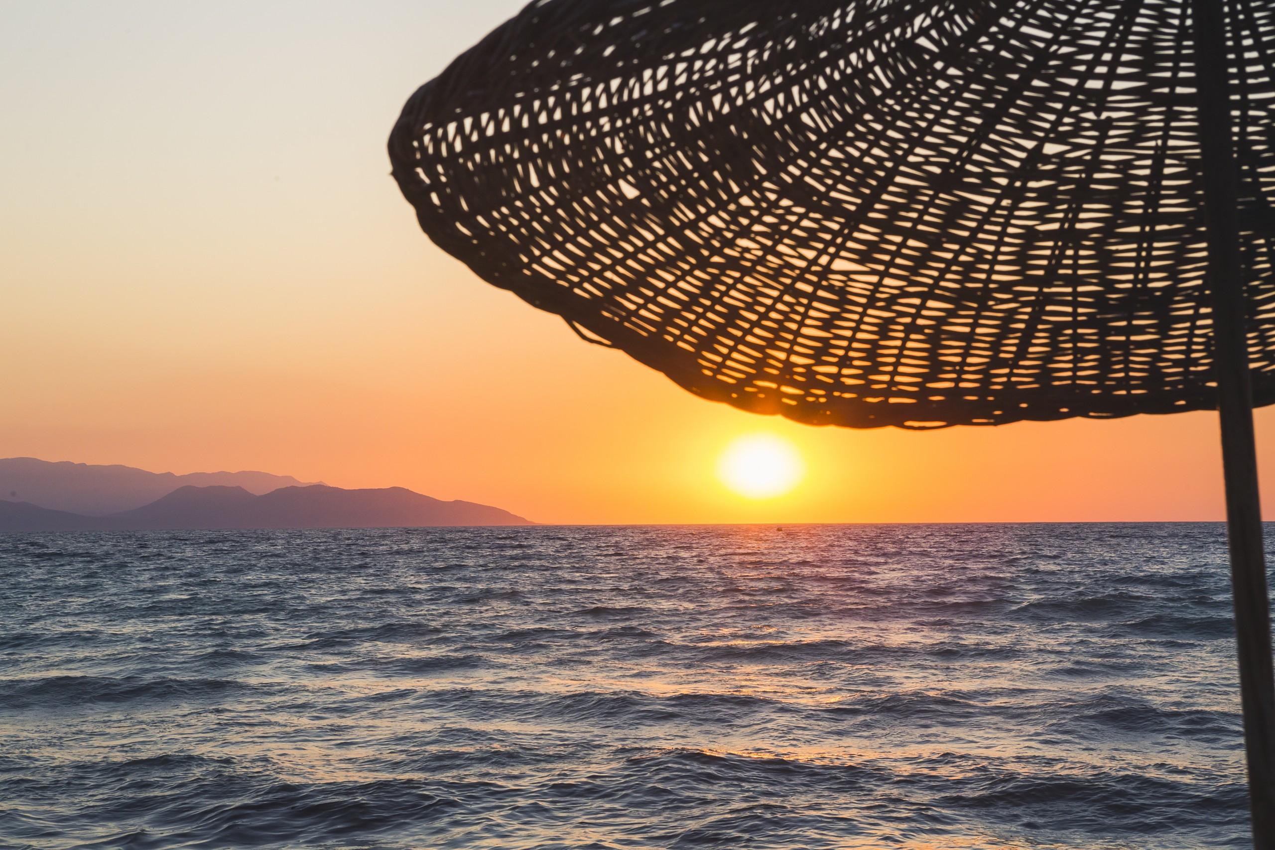 Straw umbrella and sunset